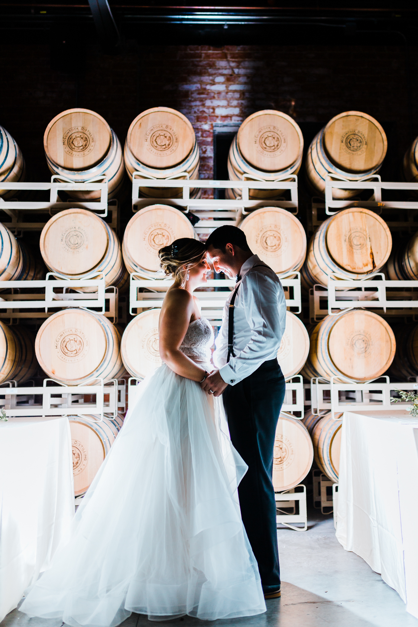 bride and groom kiss in industrial distillery - cinematic movie like wedding videographer in Maryland
