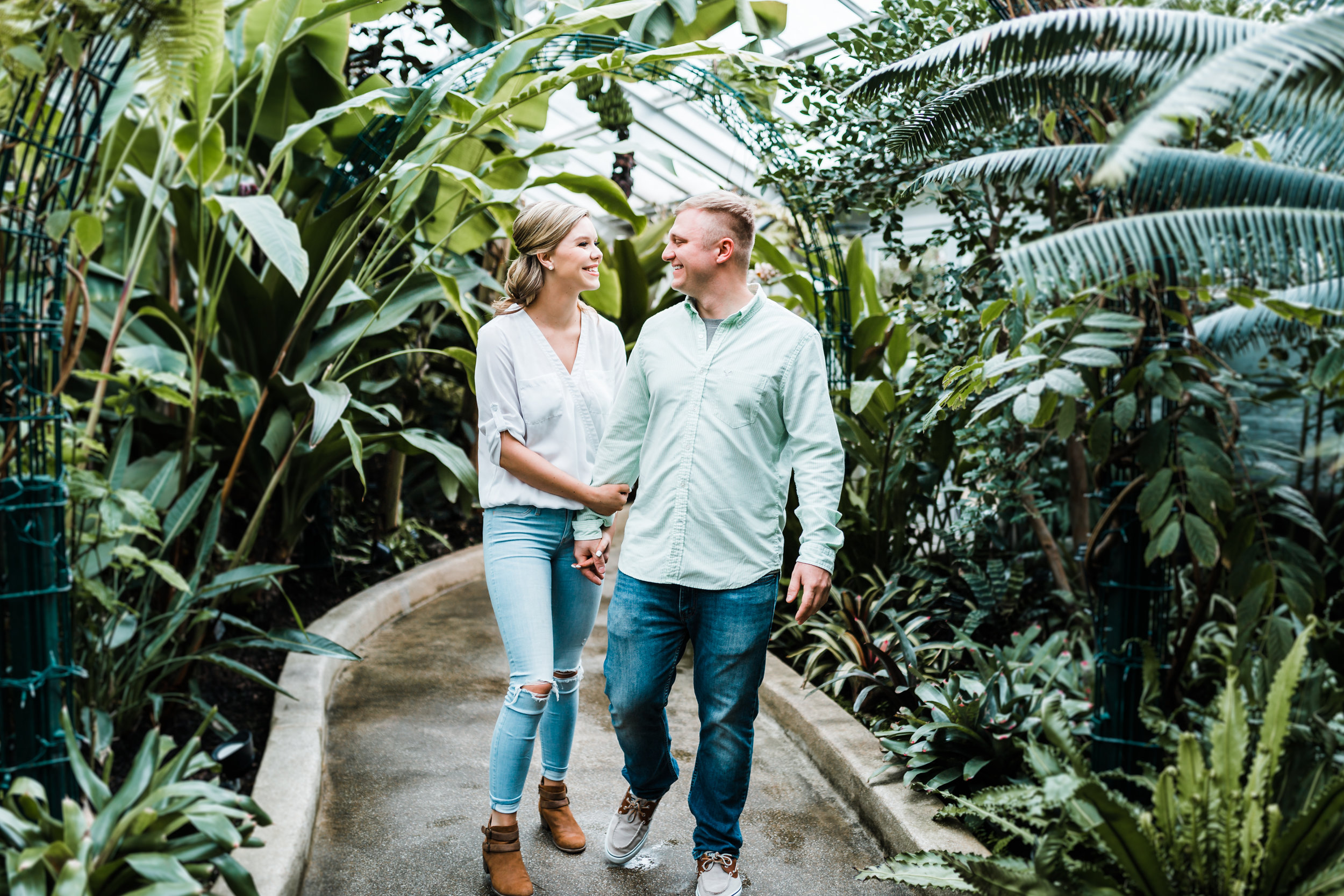 sweet couple holding hands at Rawling Conservatory in Baltimore MD engagement session - top wedding photographers in Maryland