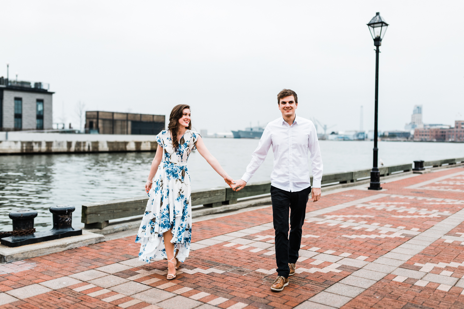 Couple walking and holding hands on promenade at Fells Point - Baltimore, Maryland engagement and wedding photographer