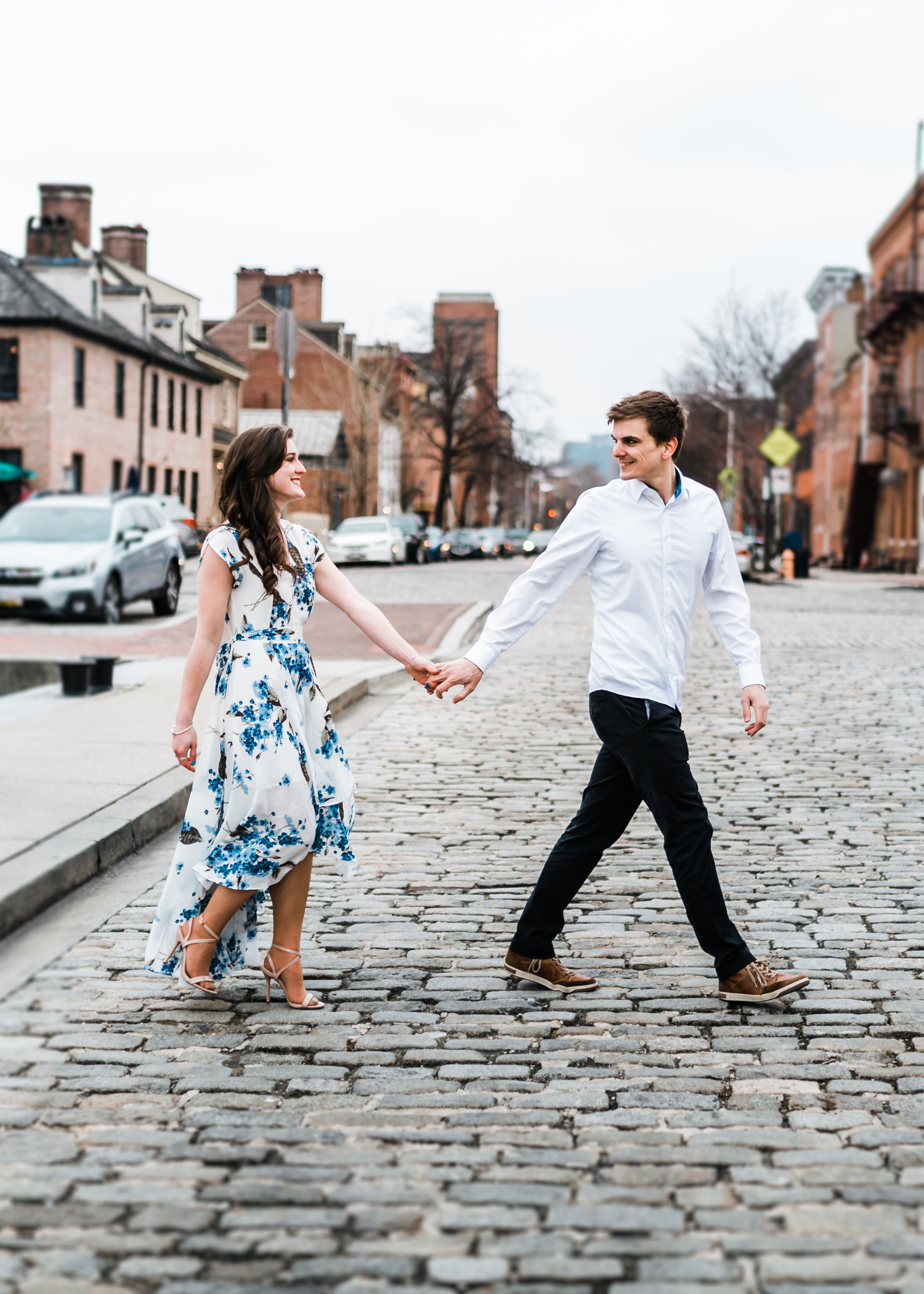 couple walking together across street in Fells Point - Baltimore engagement inspo