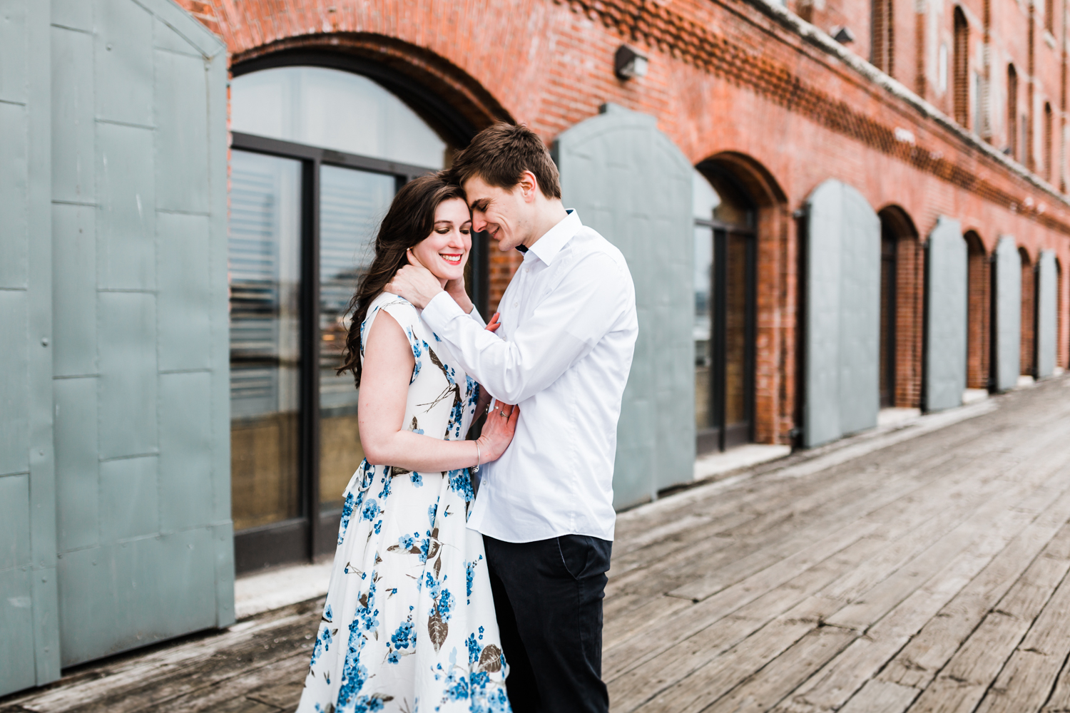 couple posing for their engagement photos on the pier in Fells Point - Baltimore, MD