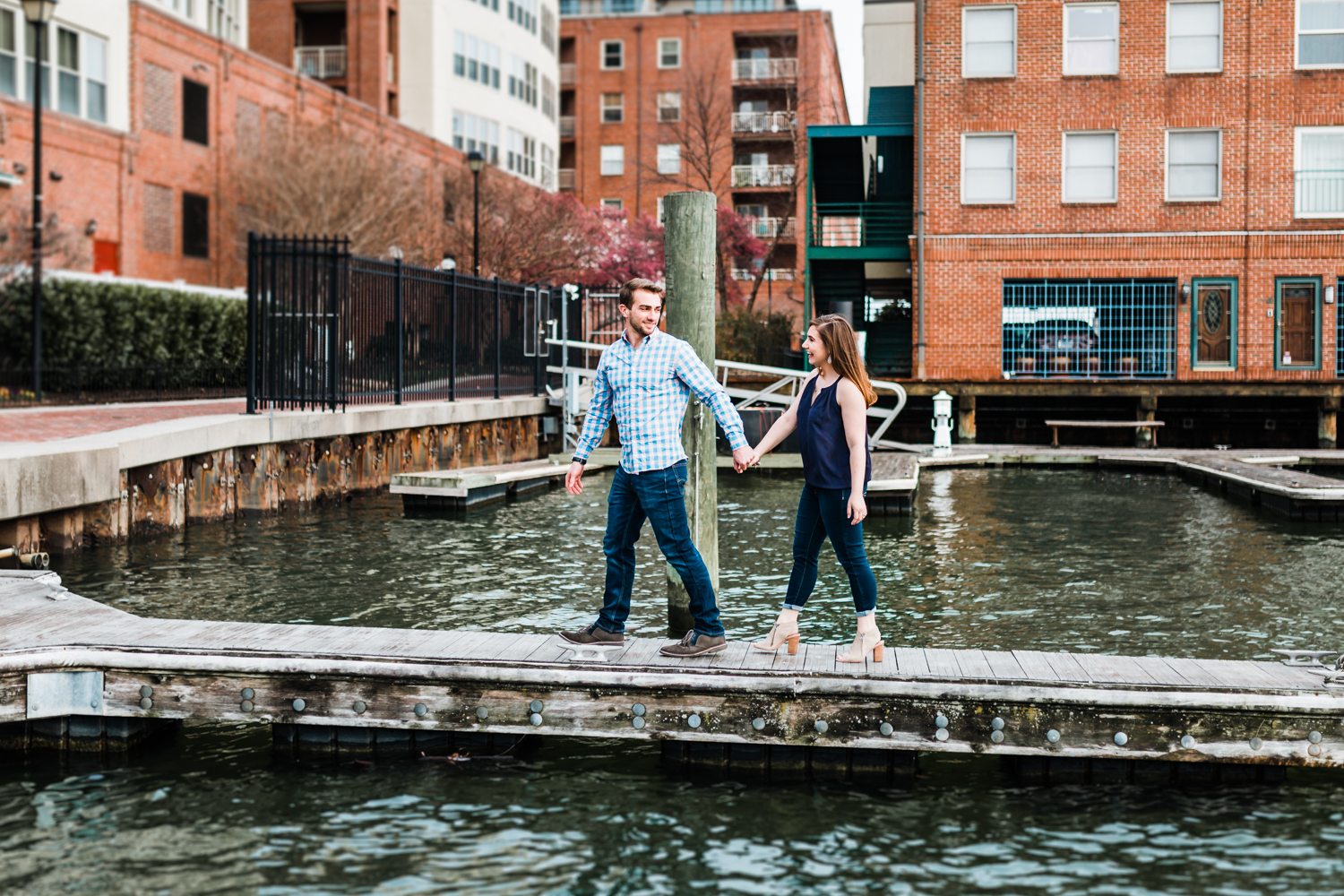 couple walking and holding hands on docks at Fells Point engagement session