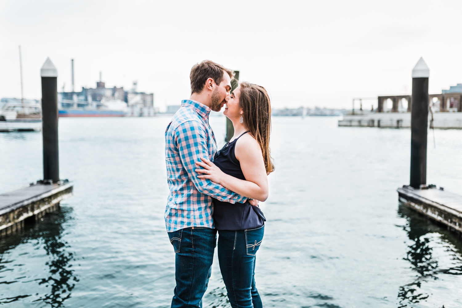 couple kissing at waterfront in Fells Point - best rated Baltimore wedding photographer