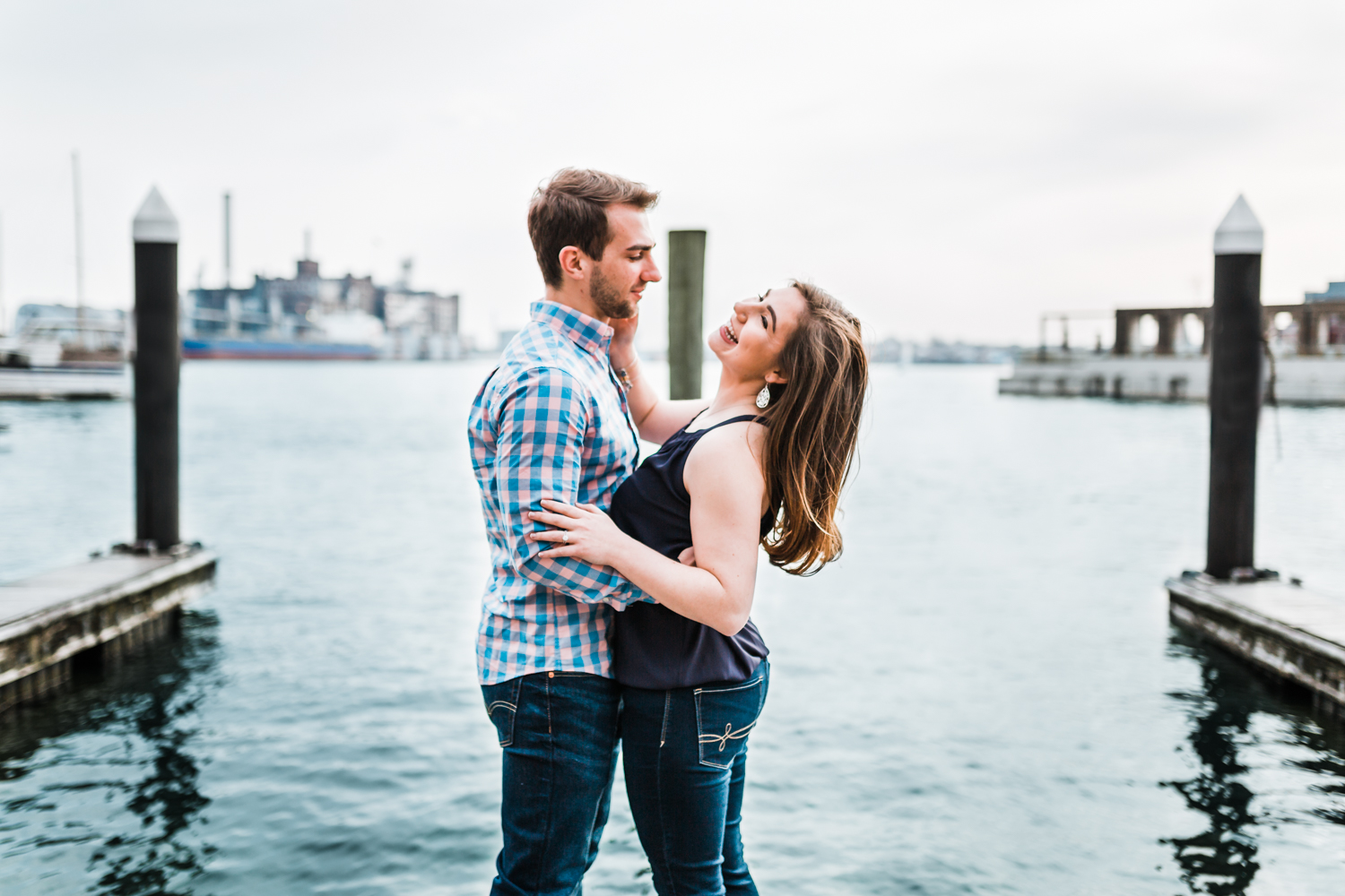 couple laughing in Fells Point during their engagement session - husband and wife photo film team in Maryland
