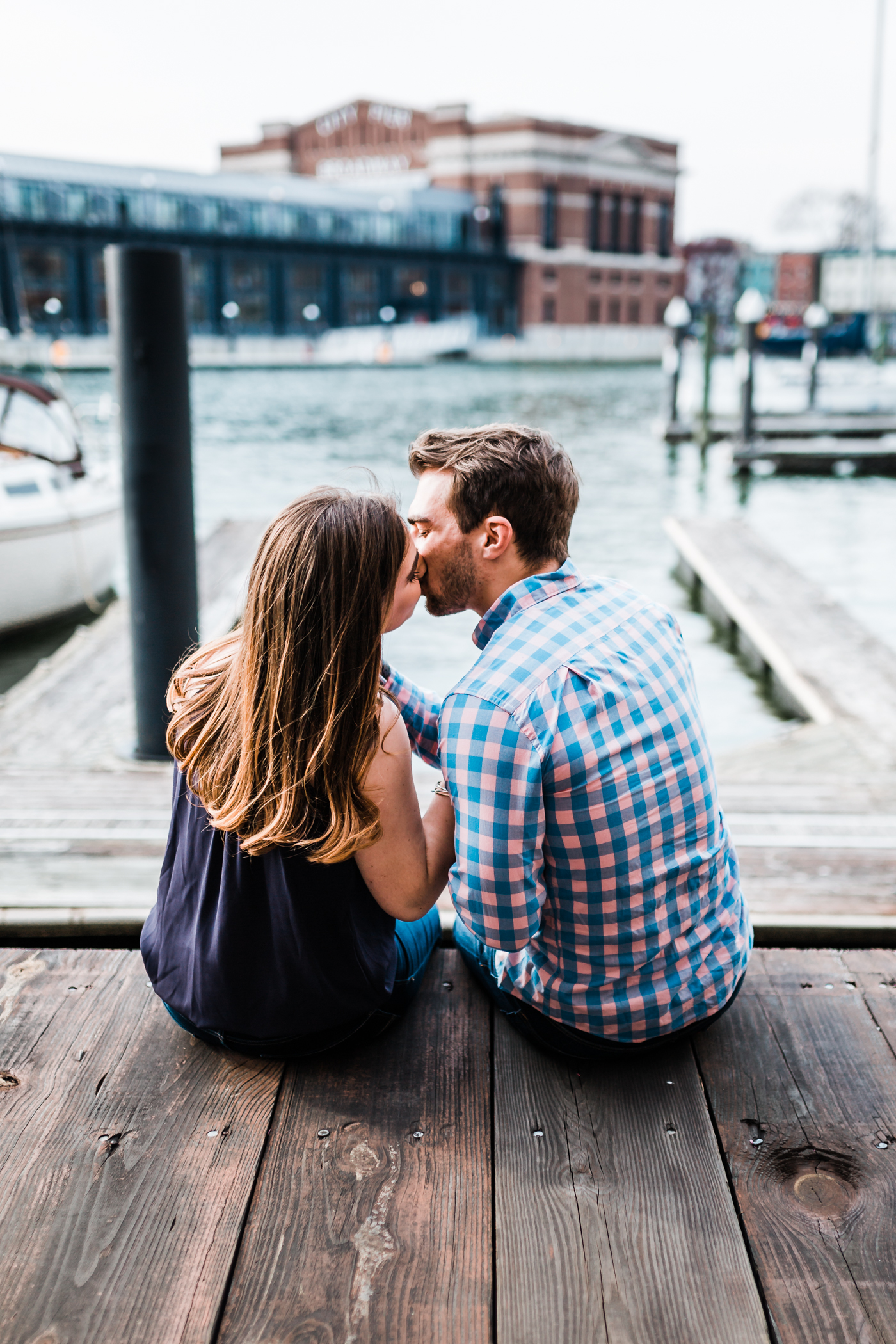 couple kissing on the docks in Fells Point - highly recommended Baltimore wedding photographer and cinematographer