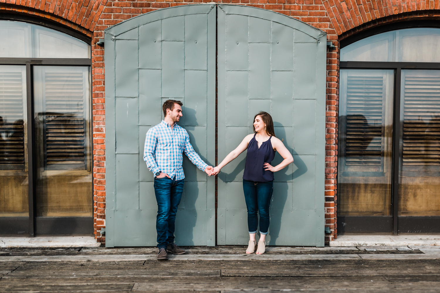 couple holding hands in Fells Point for their engagement session