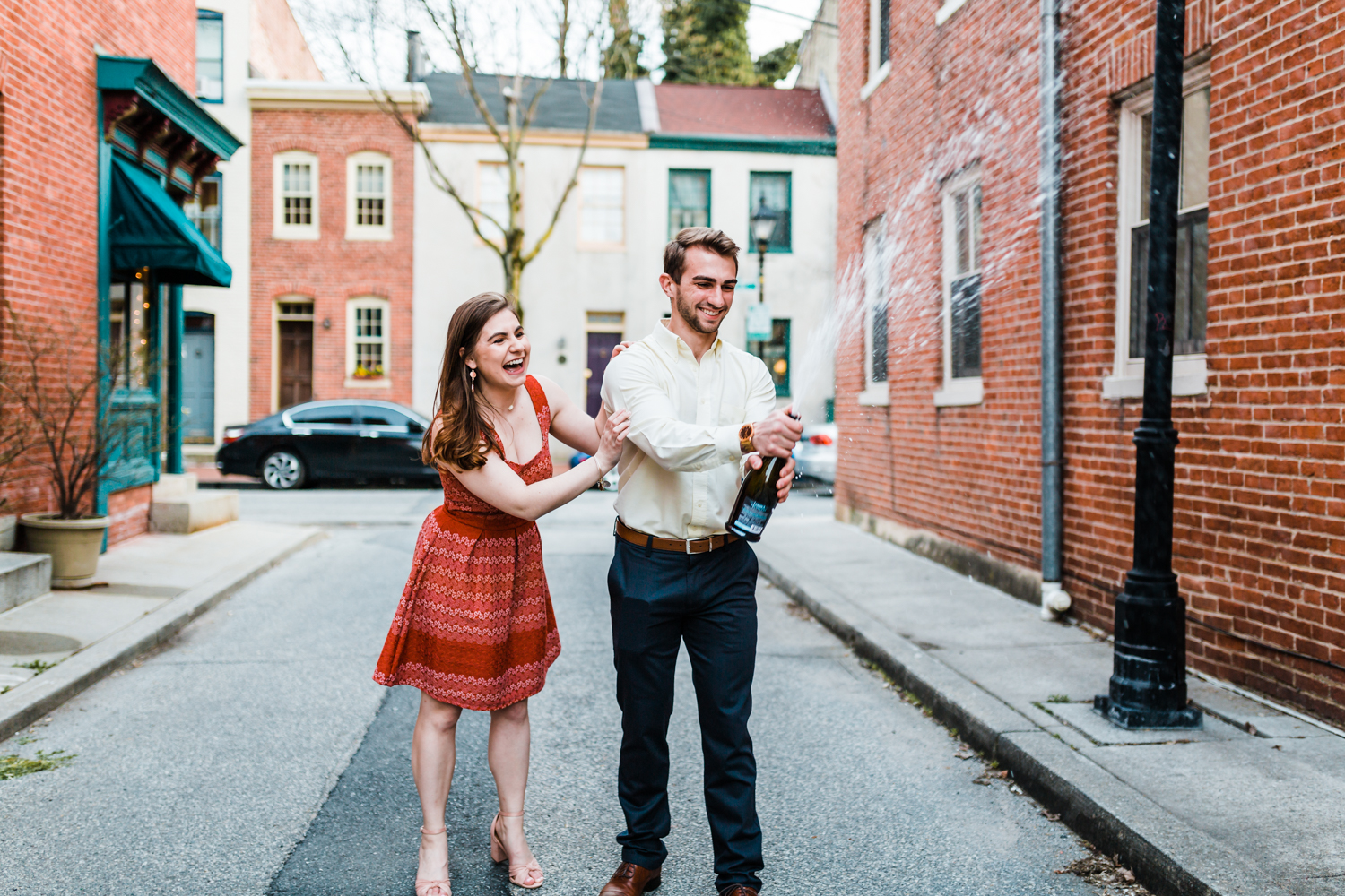 couple pops a champagne bottle during their engagement session in Baltimore