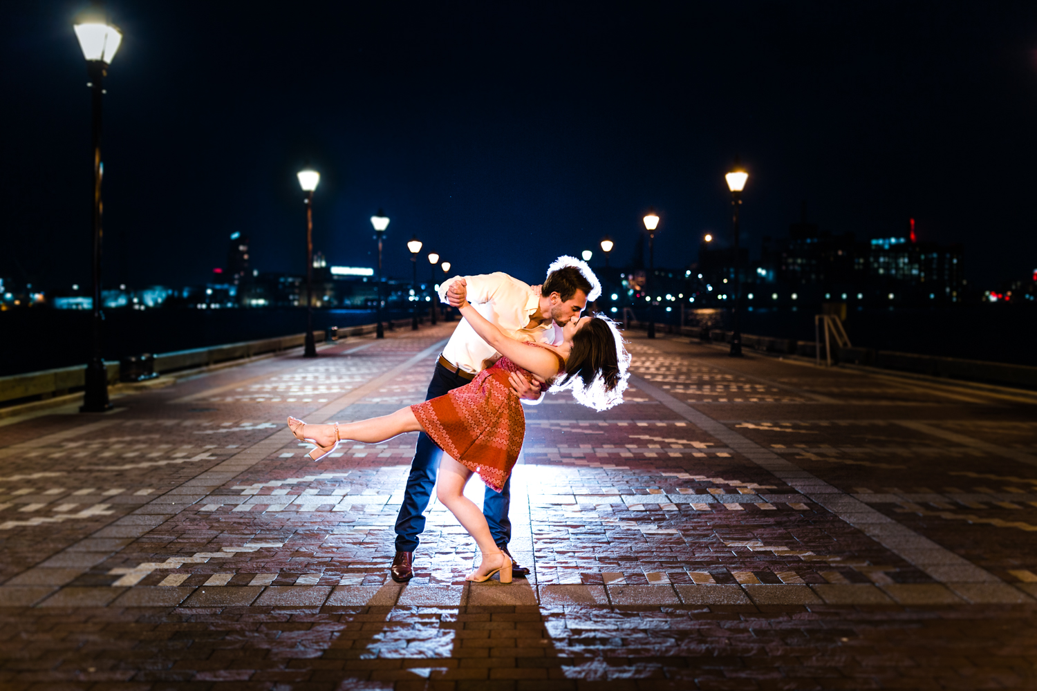 couple poses in fells point at night for their engagement session