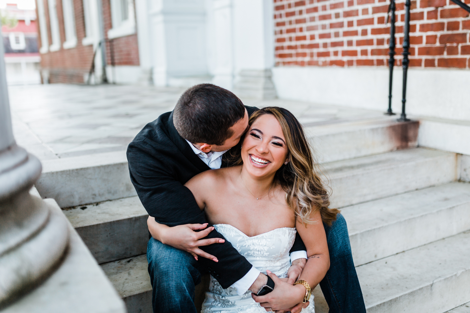 bride and groom laughing on the steps of the state house in Annapolis Maryland