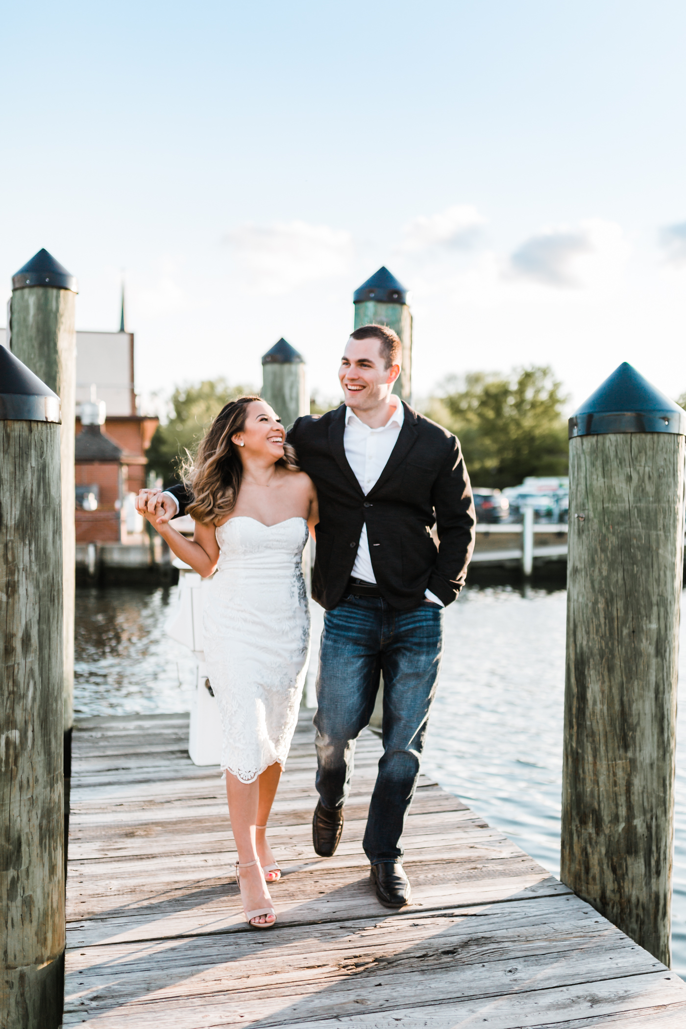 couple walking together and laughing in downtown annapolis on docks
