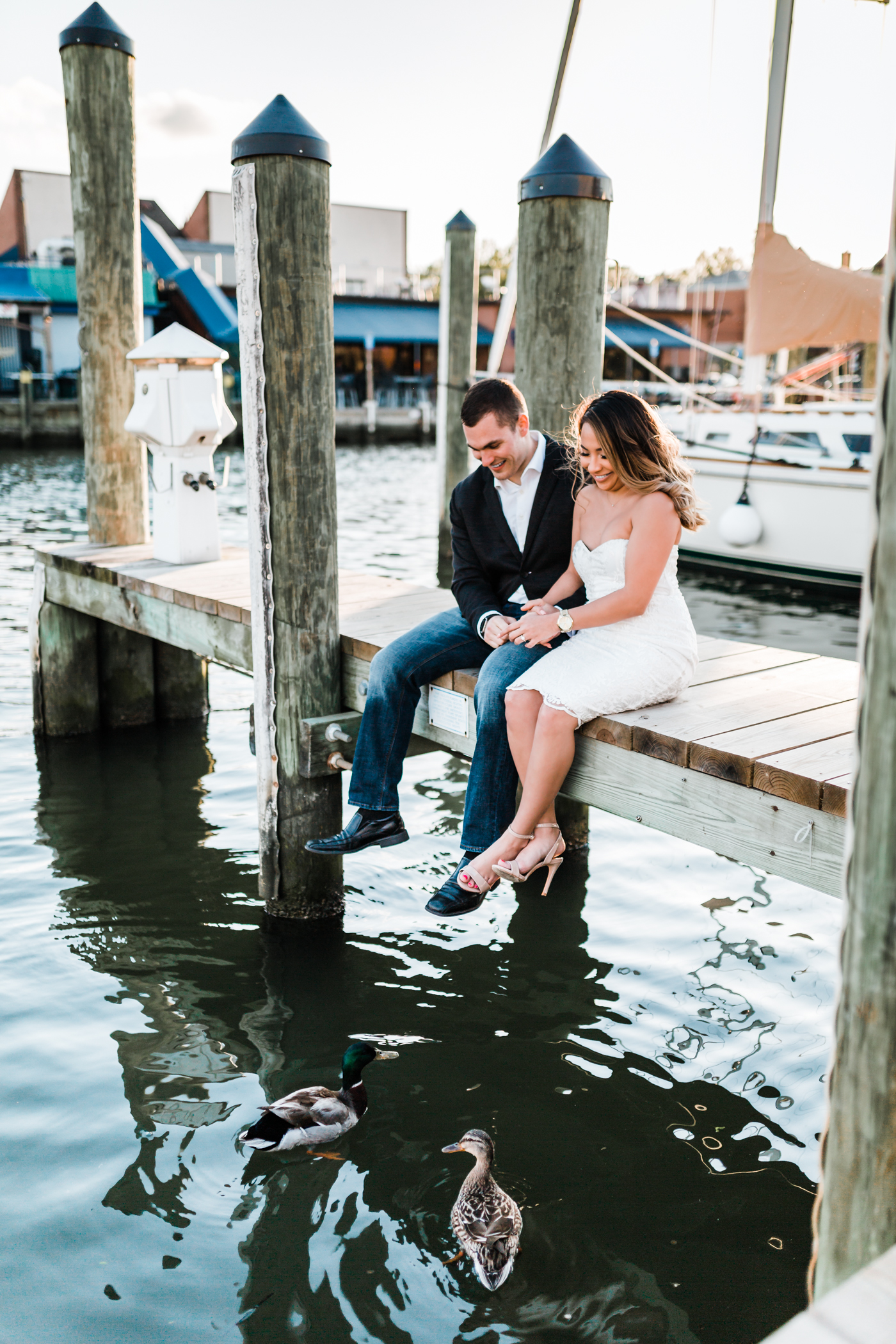 couple sitting on the dock in Annapolis and two ducks come to say hello