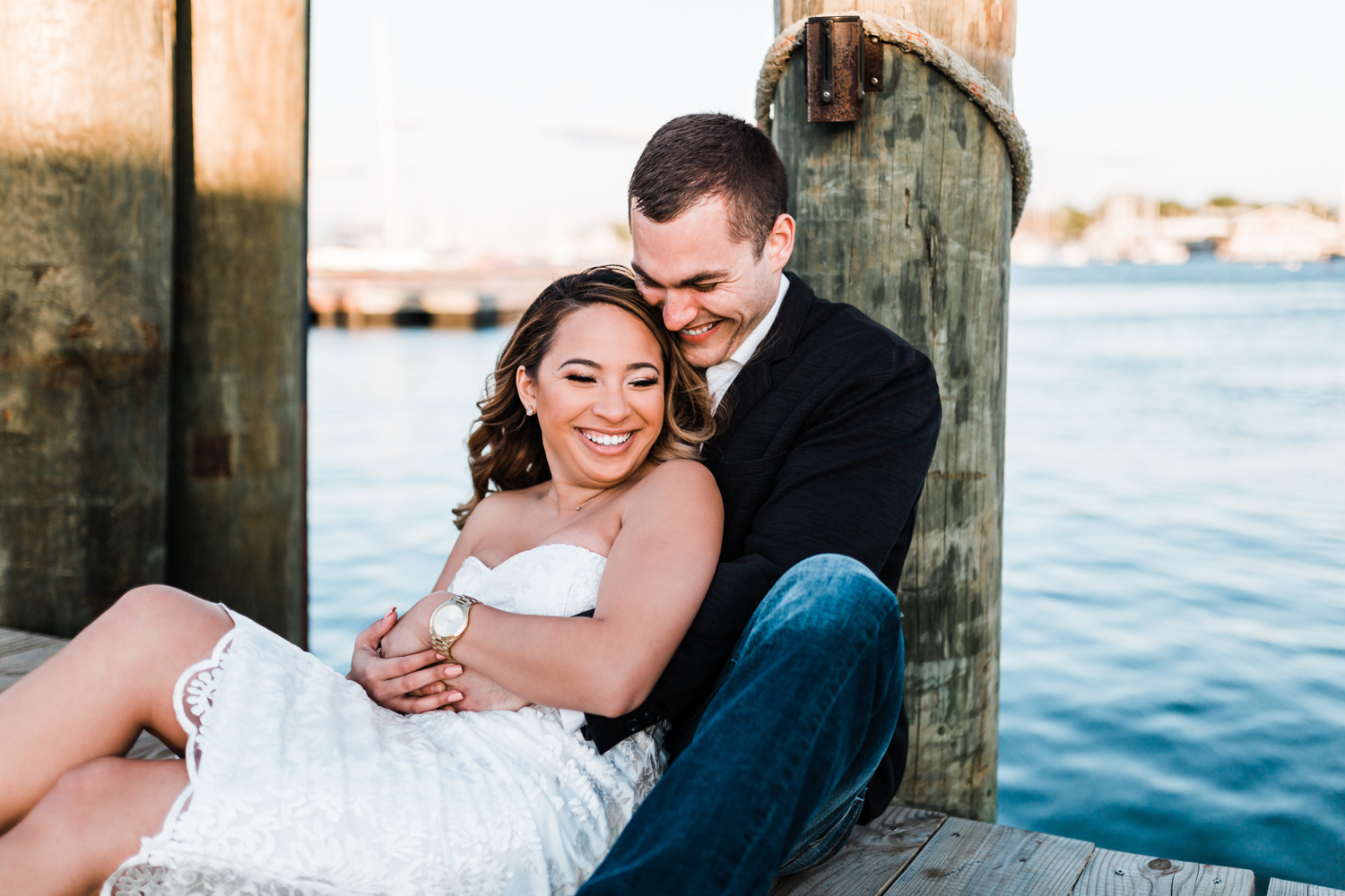 couple snuggling and laughing together in Annapolis, MD by the water