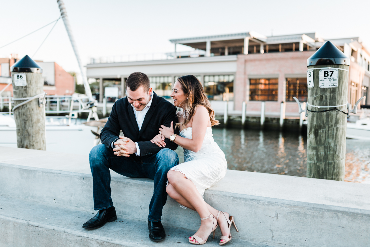 Couple laughing near boats in Downtown Annapolis - engagement session with boats and ships in Maryland