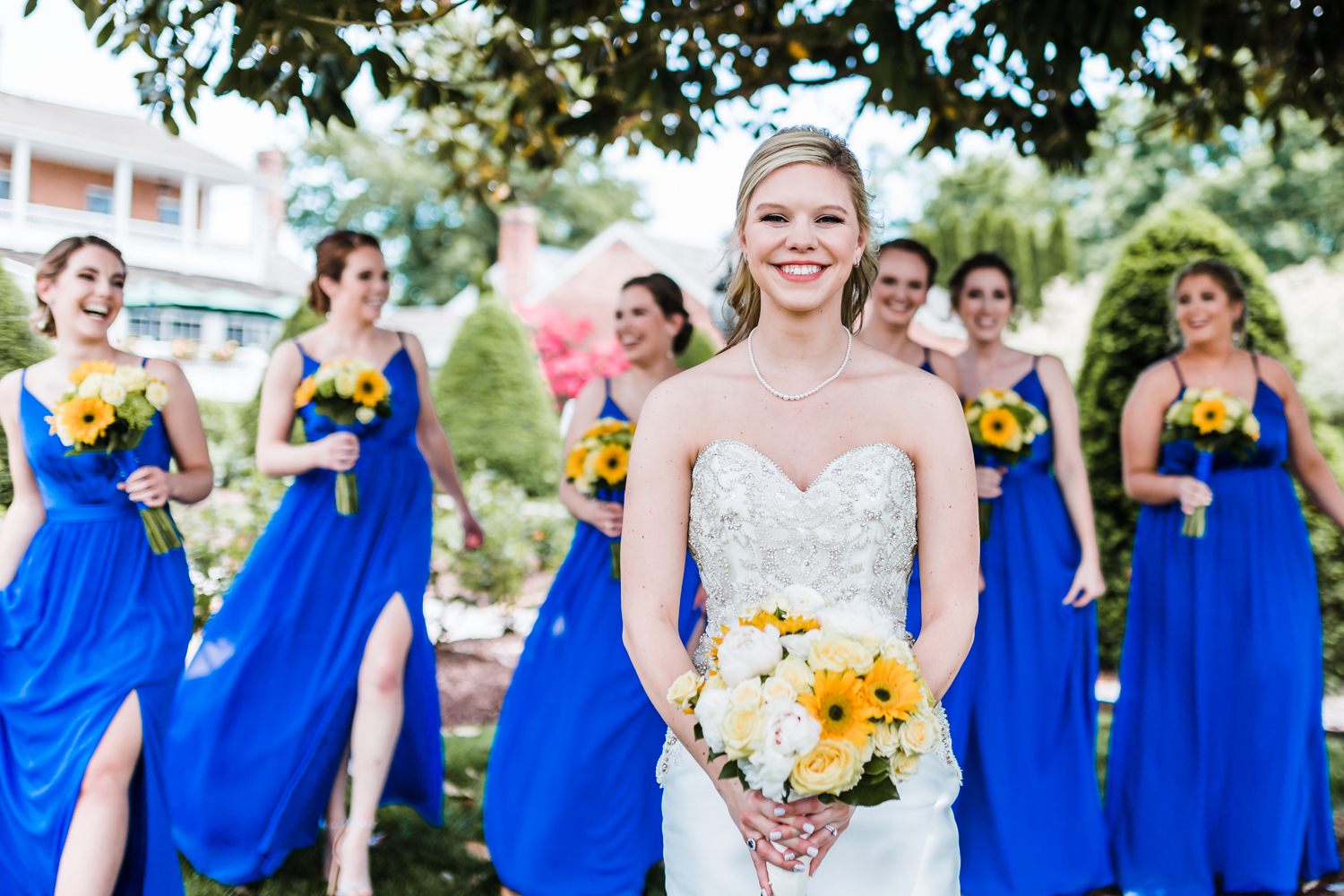 bride smiling with bridesmaids in back - beautiful classy venue in Maryland
