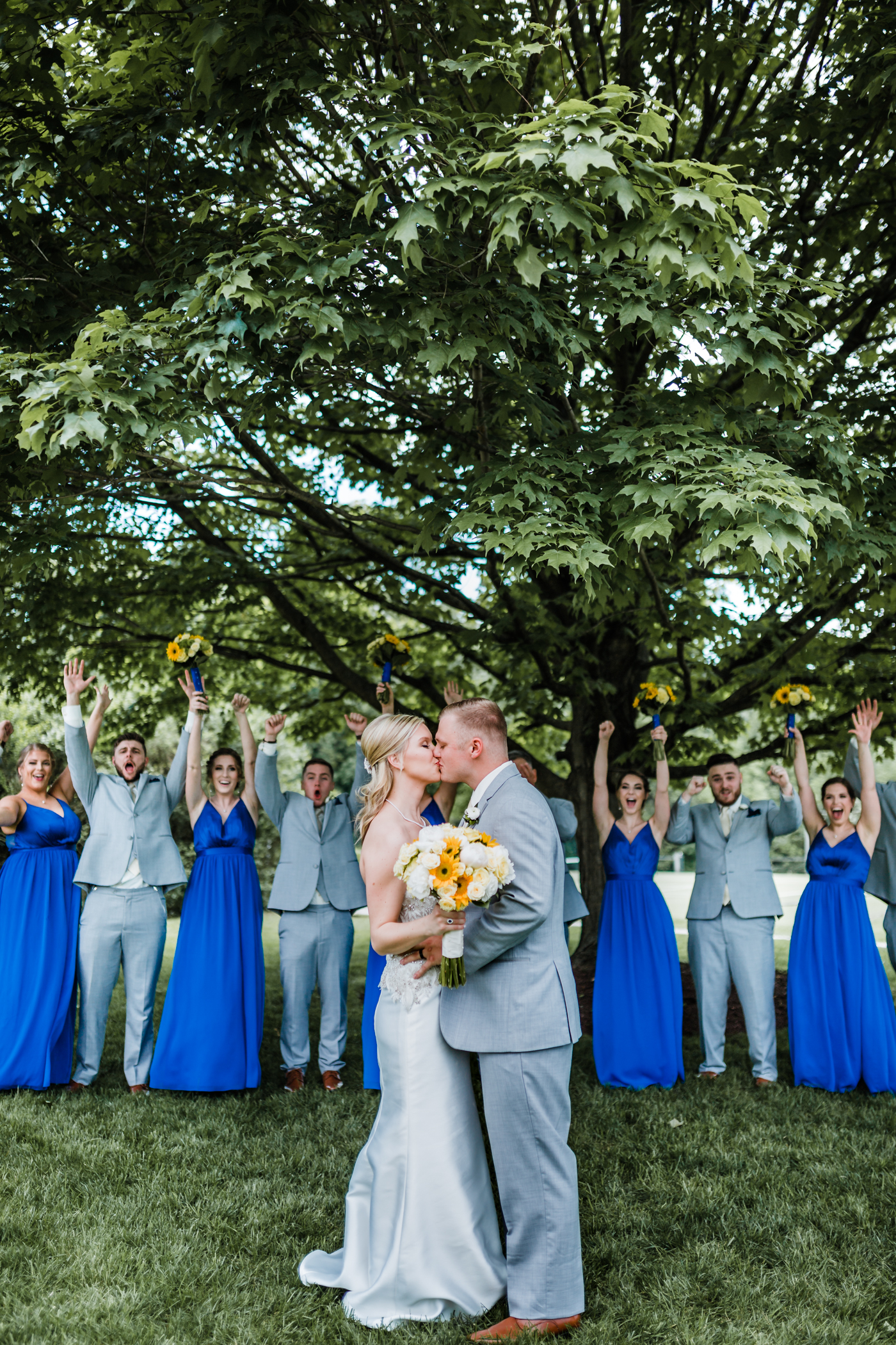 bride and groom kiss in front of cheering wedding party - top husband and wife photography team