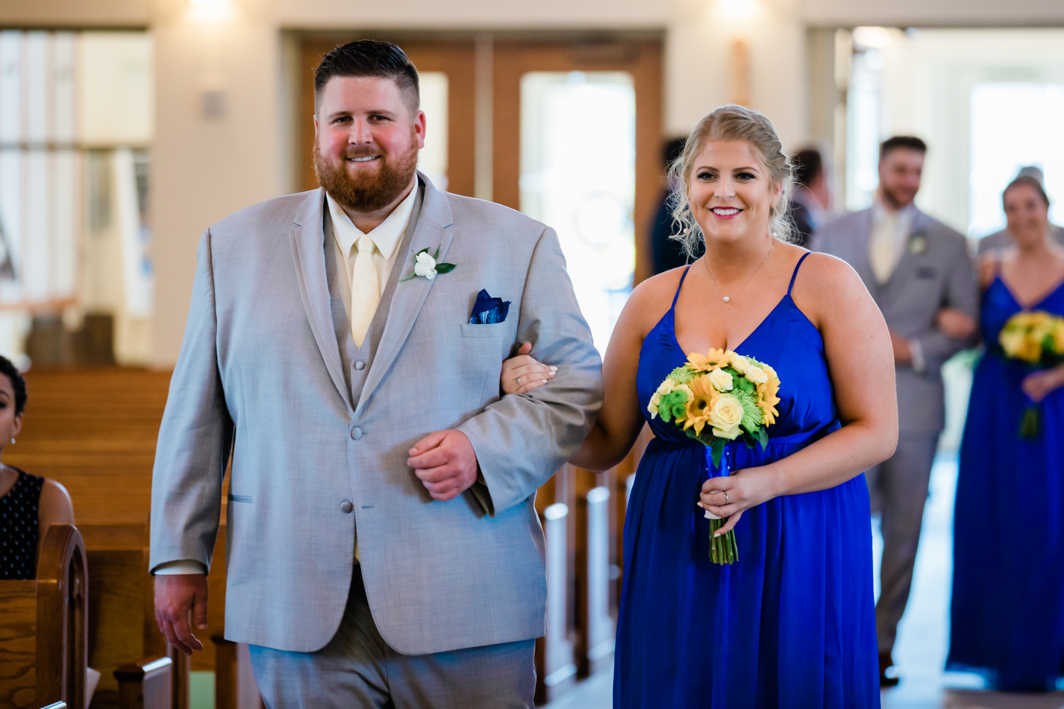 bridal party makes their way down the aisle at church in Westminster, MD - royal blue and yellow wedding color scheme
