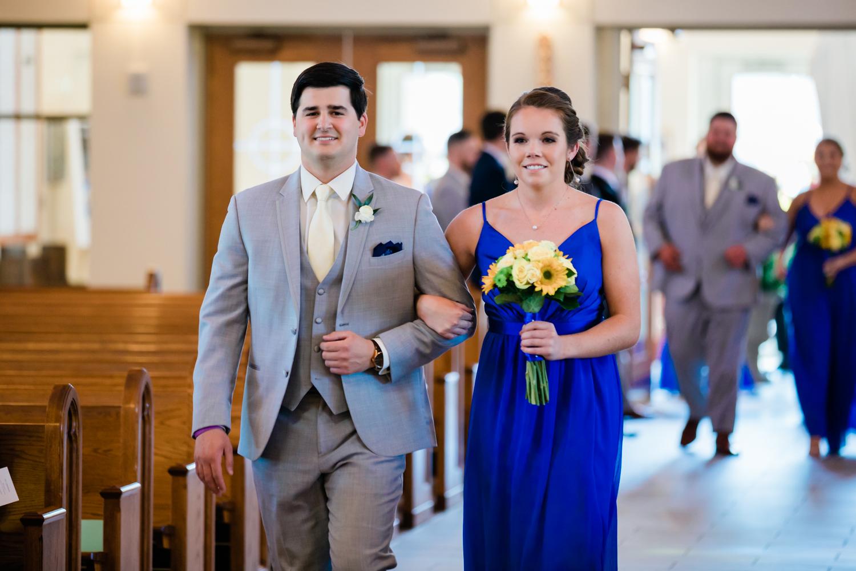 bridesmaid and groomsman walking down the aisle at catholic wedding in Maryland