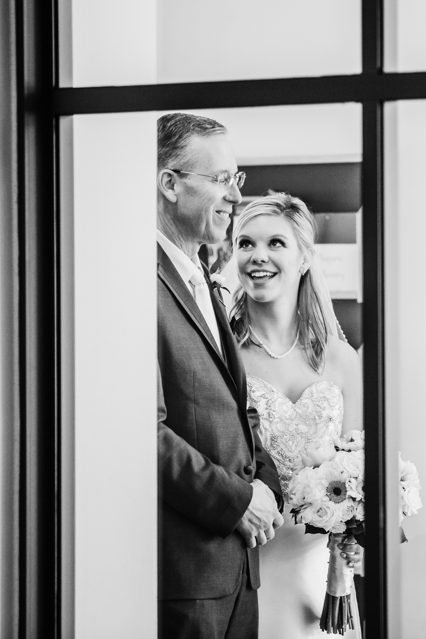 bride smiles at her father before they walk down the aisle - maryland wedding photographer and cinematographer