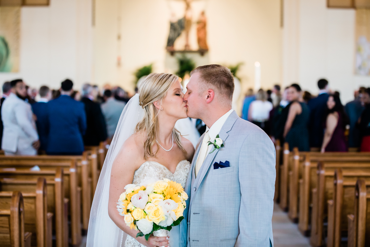 bride and groom share one last kiss before exiting the church