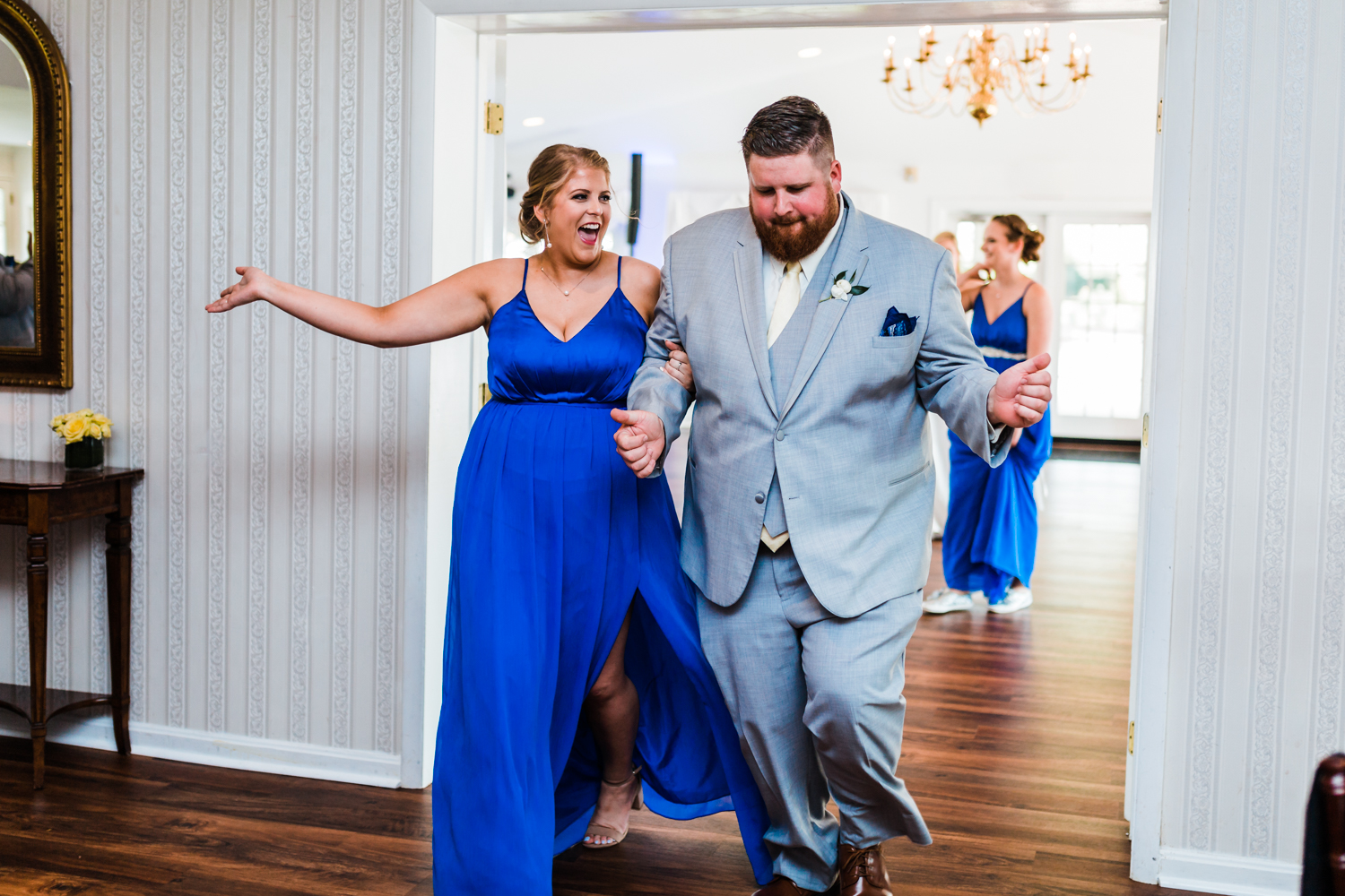 groomsman and bridesmaid walking into reception - best photographer in MD