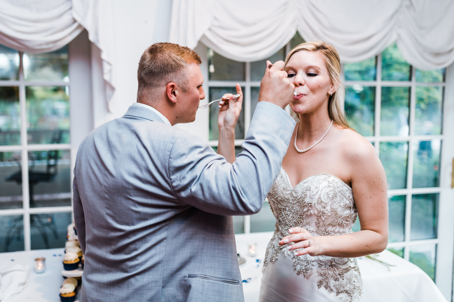 mr and mrs eating their wedding cake - top wedding venues with a garden estate setting in Maryland