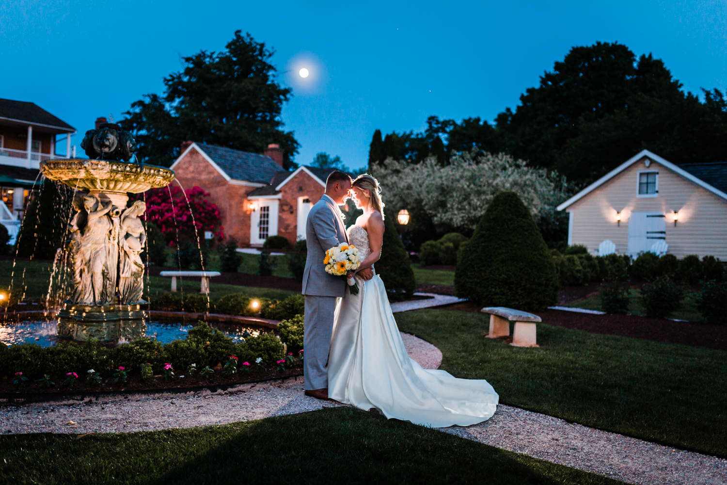 newlyweds pose in front of the fountain at Antrim 1844 with the super moon - Carroll County MD wedding photographer and cinematographer husband and wife team