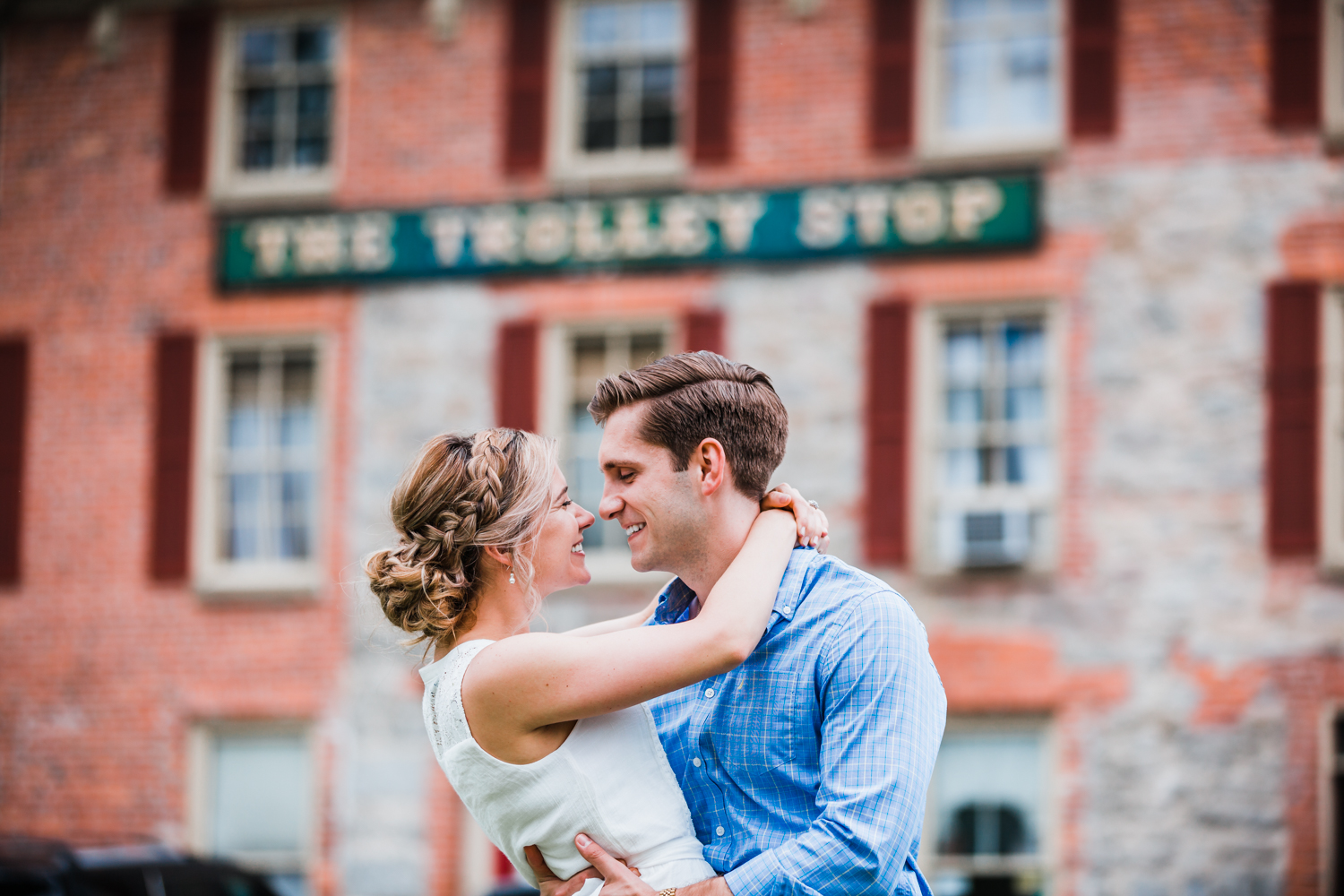 couple poses in front of the trolley stop in Ellicott City, Maryland