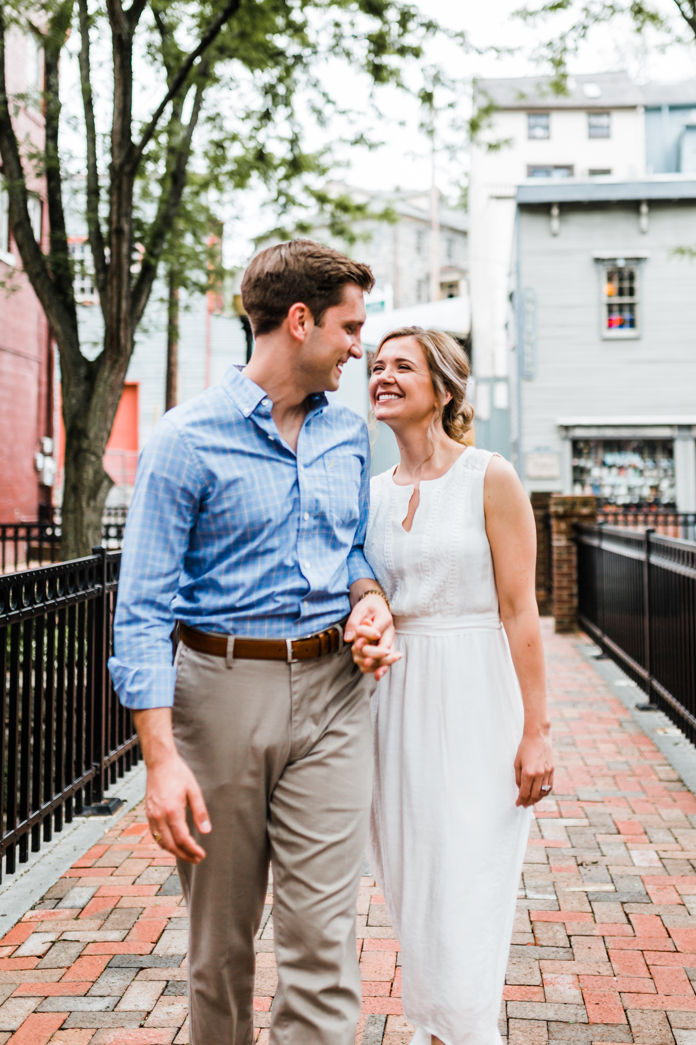 adorable couple poses in city setting in Maryland