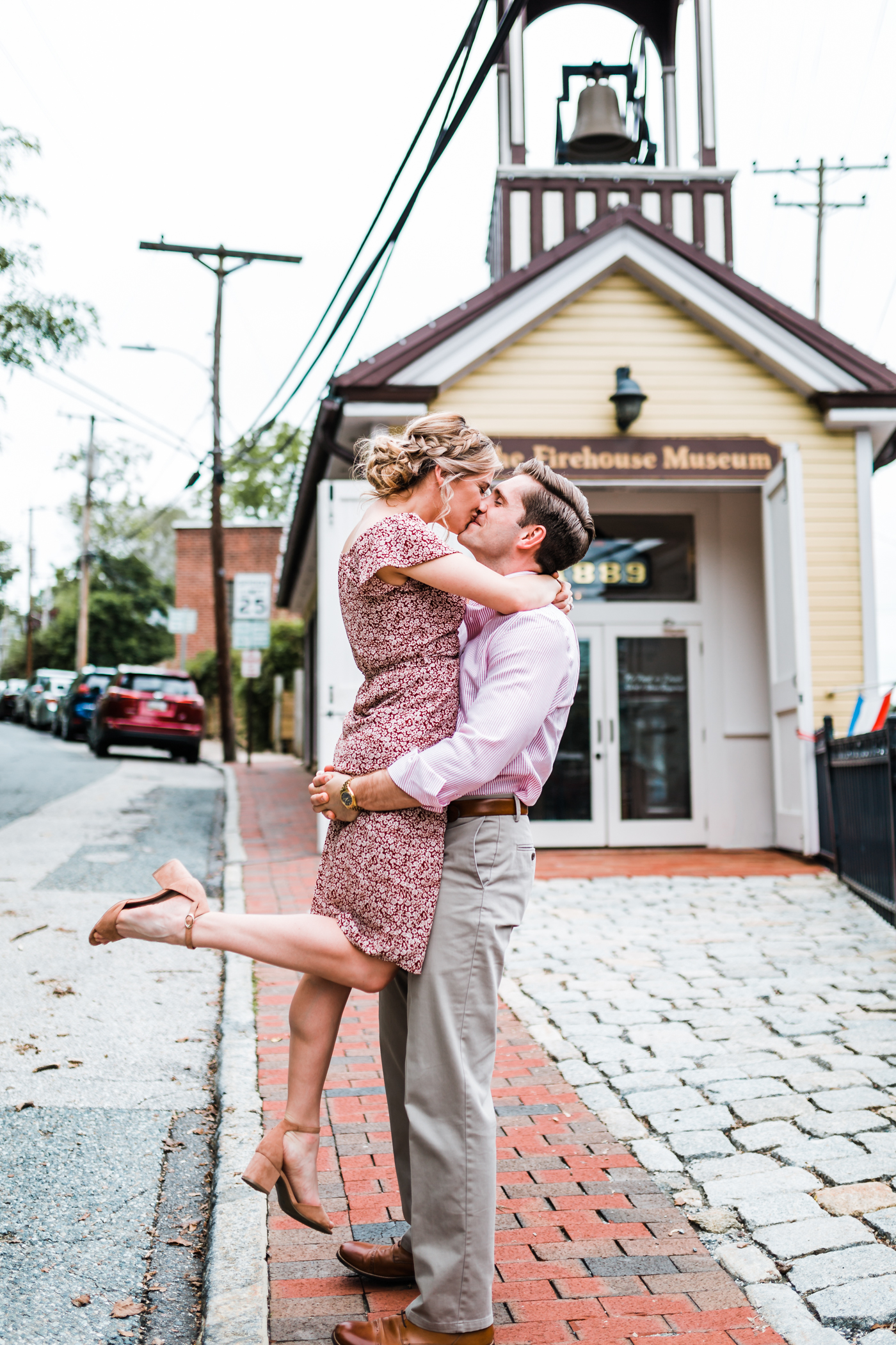 couple kissing in front of the firehouse museum in Ellicott City, MD