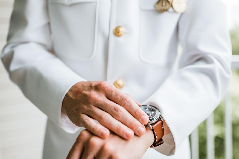 groom adjusting his watch - Maryland wedding photographer and videographer husband and wife team