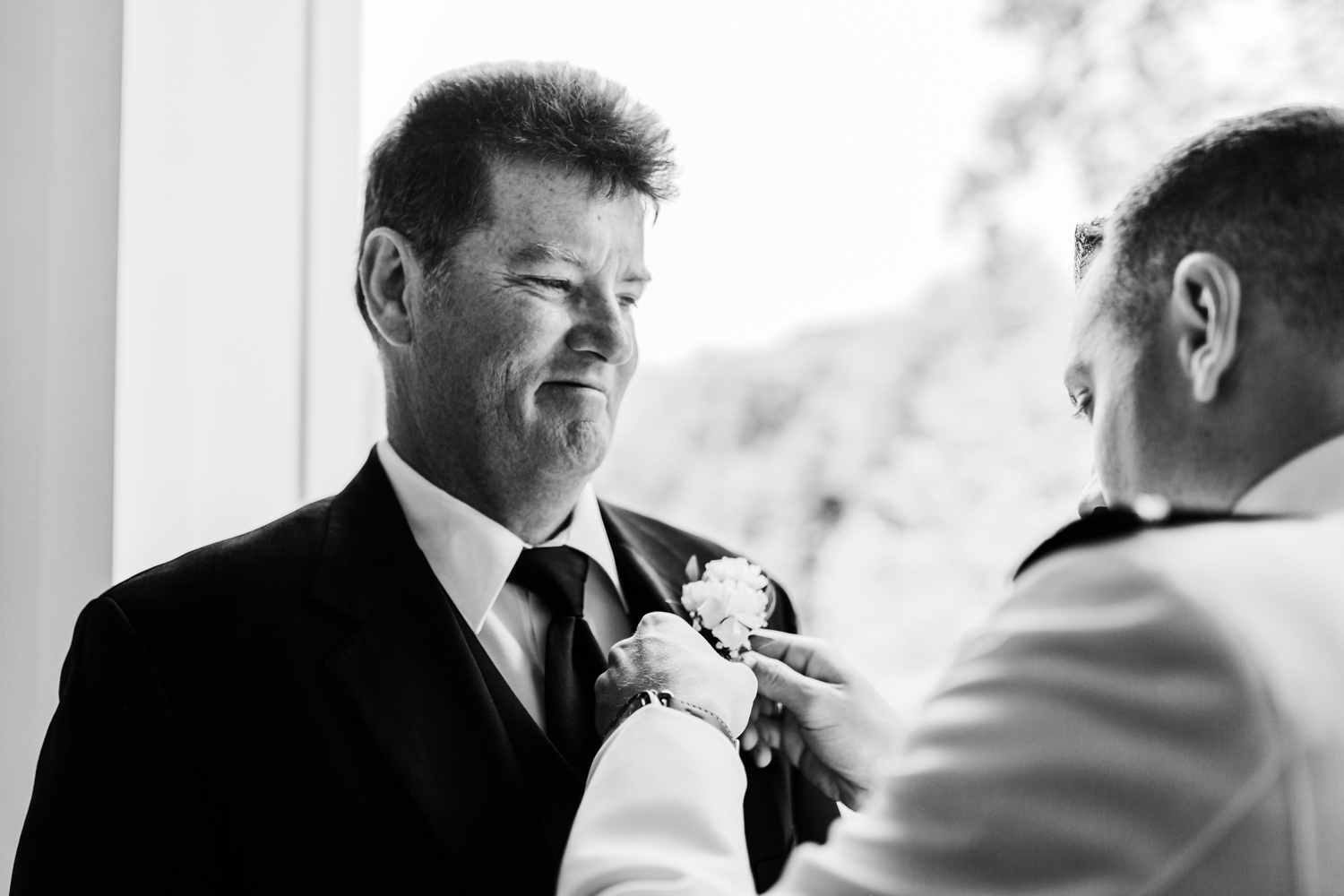 groom putting on his dad's boutonniere - maryland wedding photo and cinematography