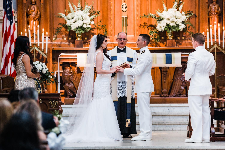 bride puts on her grooms wedding ring at Naval Academy wedding