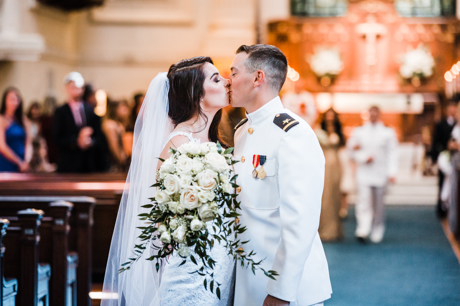 bride and groom kiss at the naval academy