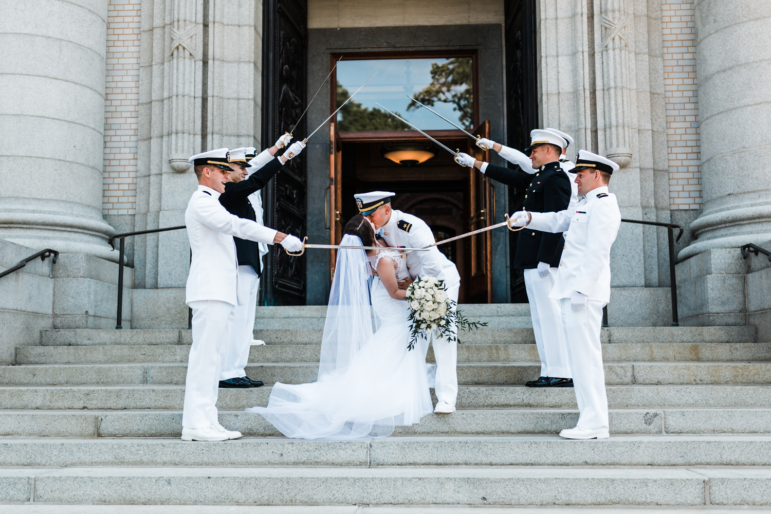 couple kiss at the sword arch at the naval academy in annapolis md
