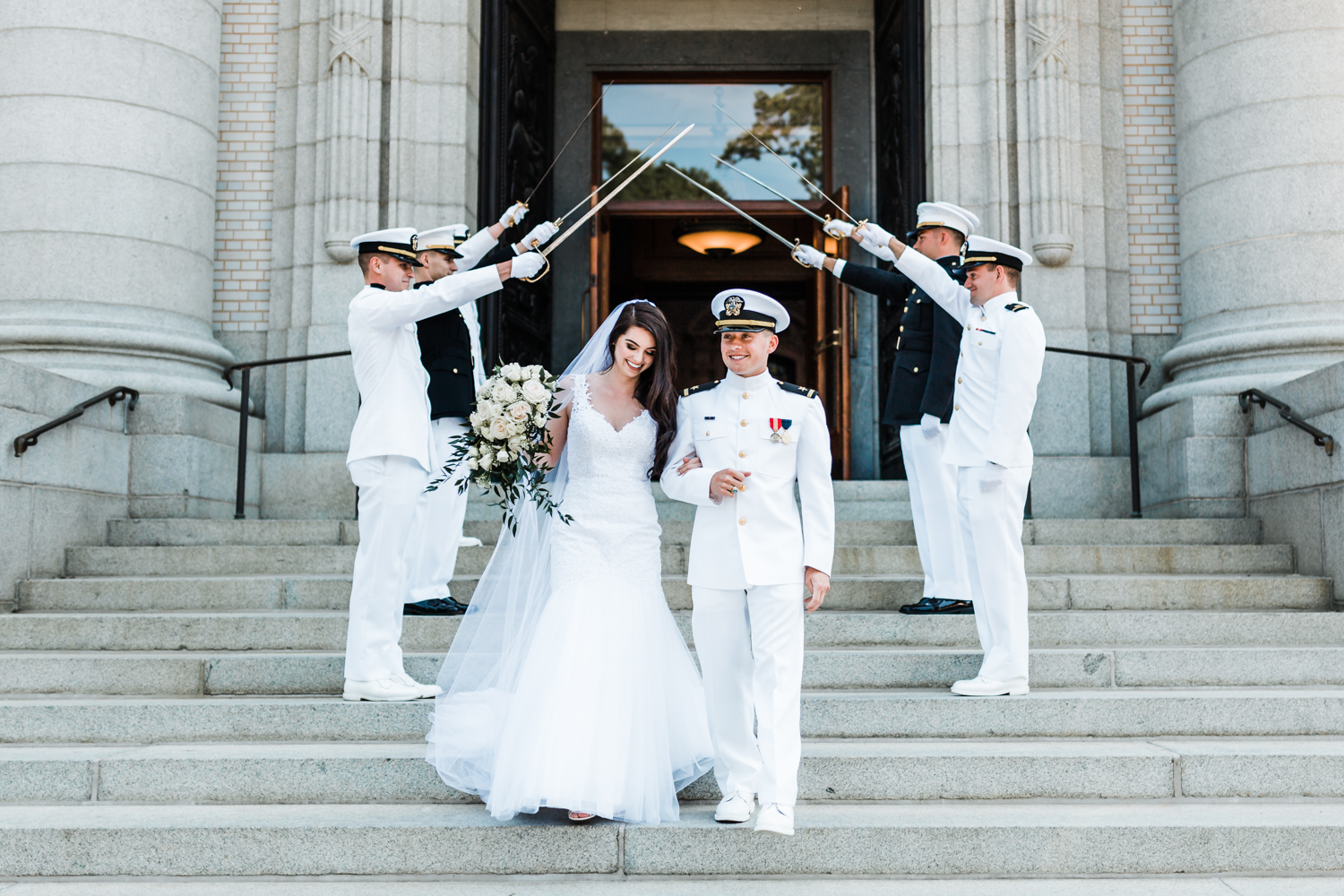 bride and groom happily exit the chapel under sword arch at Naval Academy