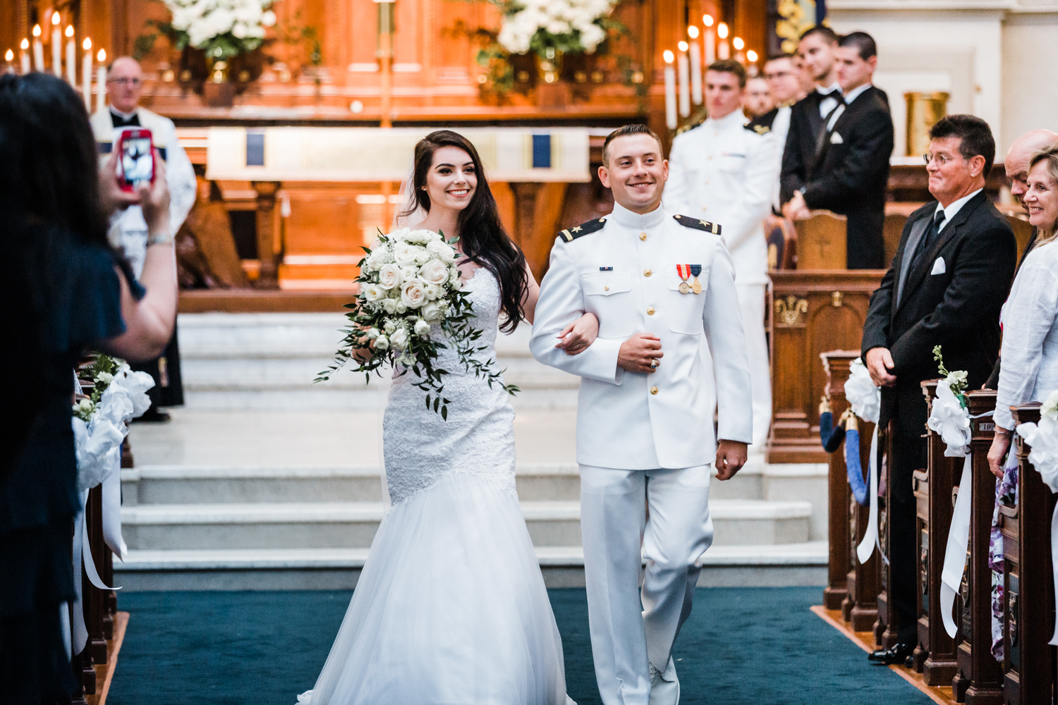 bride and groom happily walk down the aisle together after they say I Do