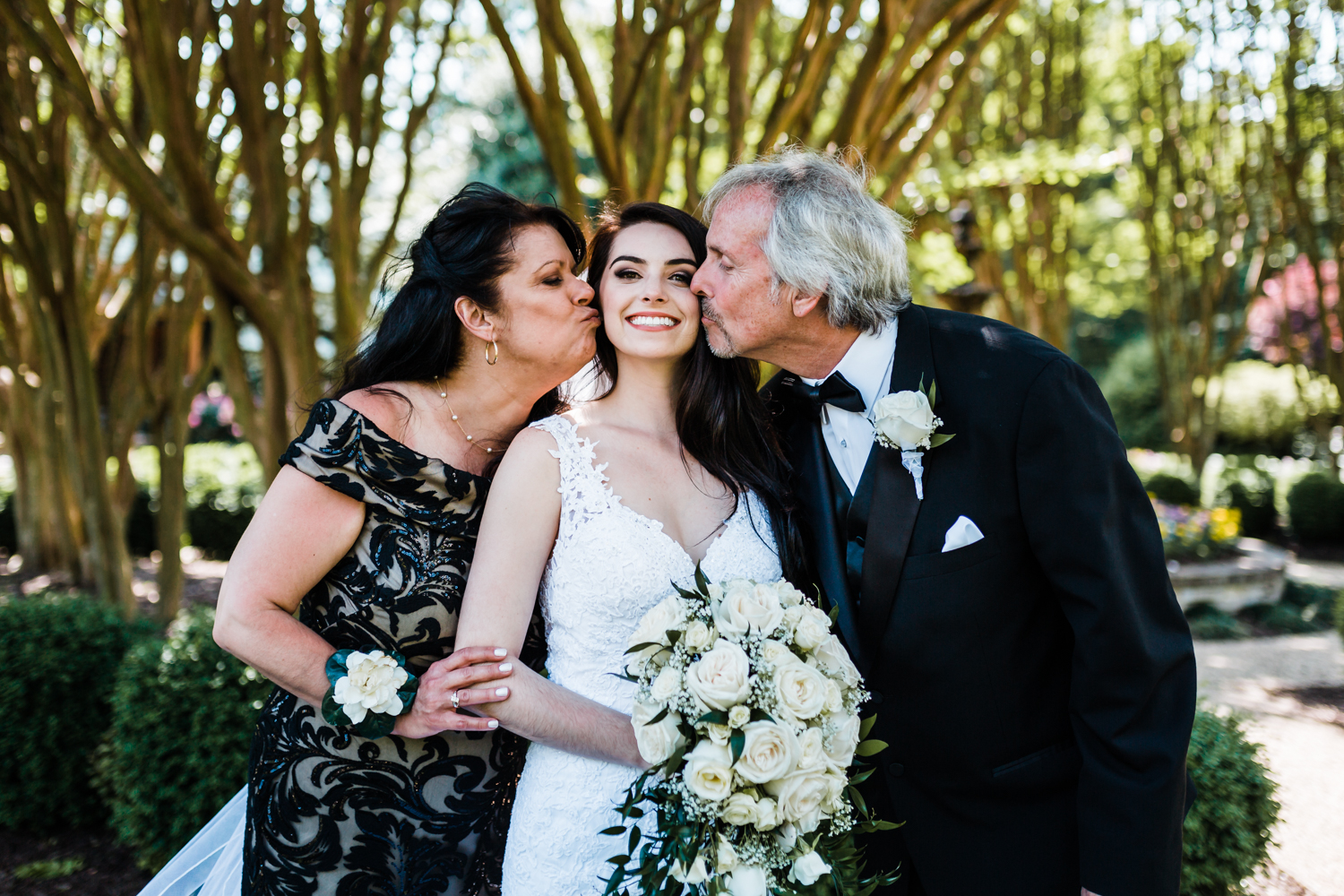 bride gets a kiss on her cheeks from her mom and dad on her wedding day in Annapolis, Maryland