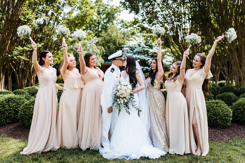 bride and groom kiss while bridesmaids cheer