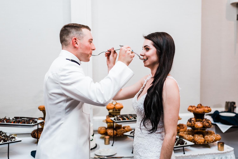 Alex and Eric feeding each other their wedding cake
