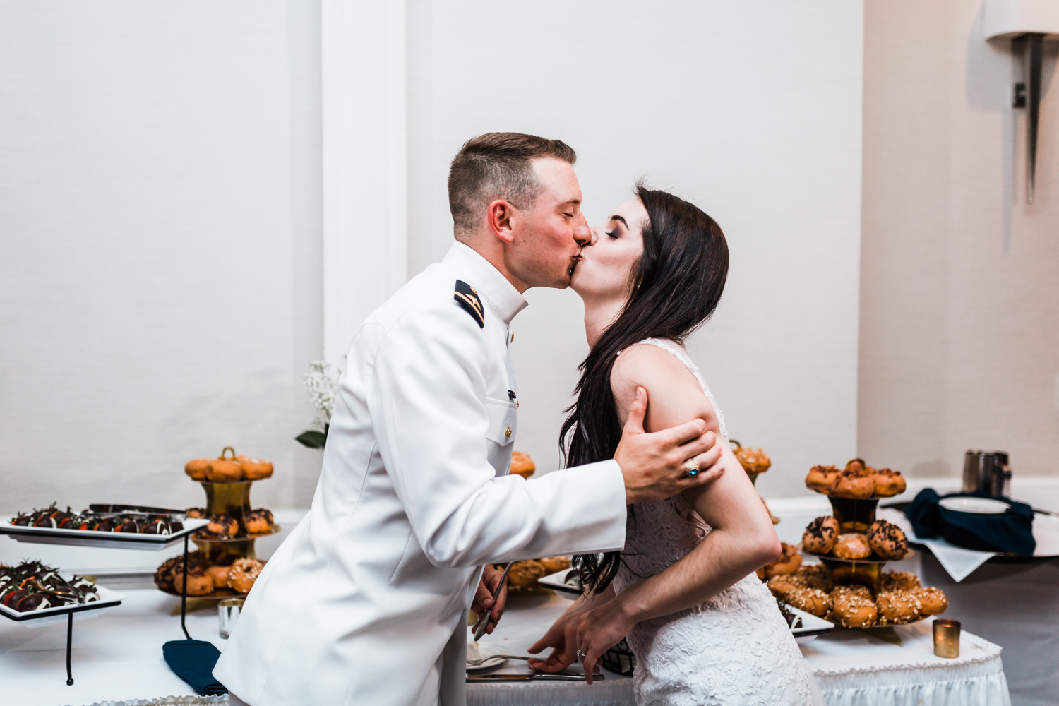 bride and groom kiss after their cake cutting