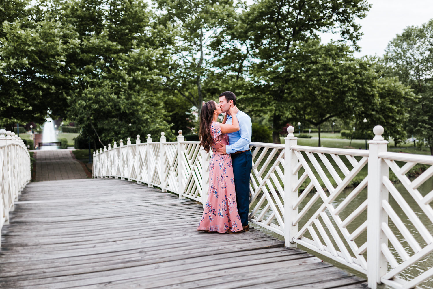 couple kissing on the bridge near the fountain in Annapolis, MD - top rated wedding and engagement photographer in Maryland - husband and wife photo and video team