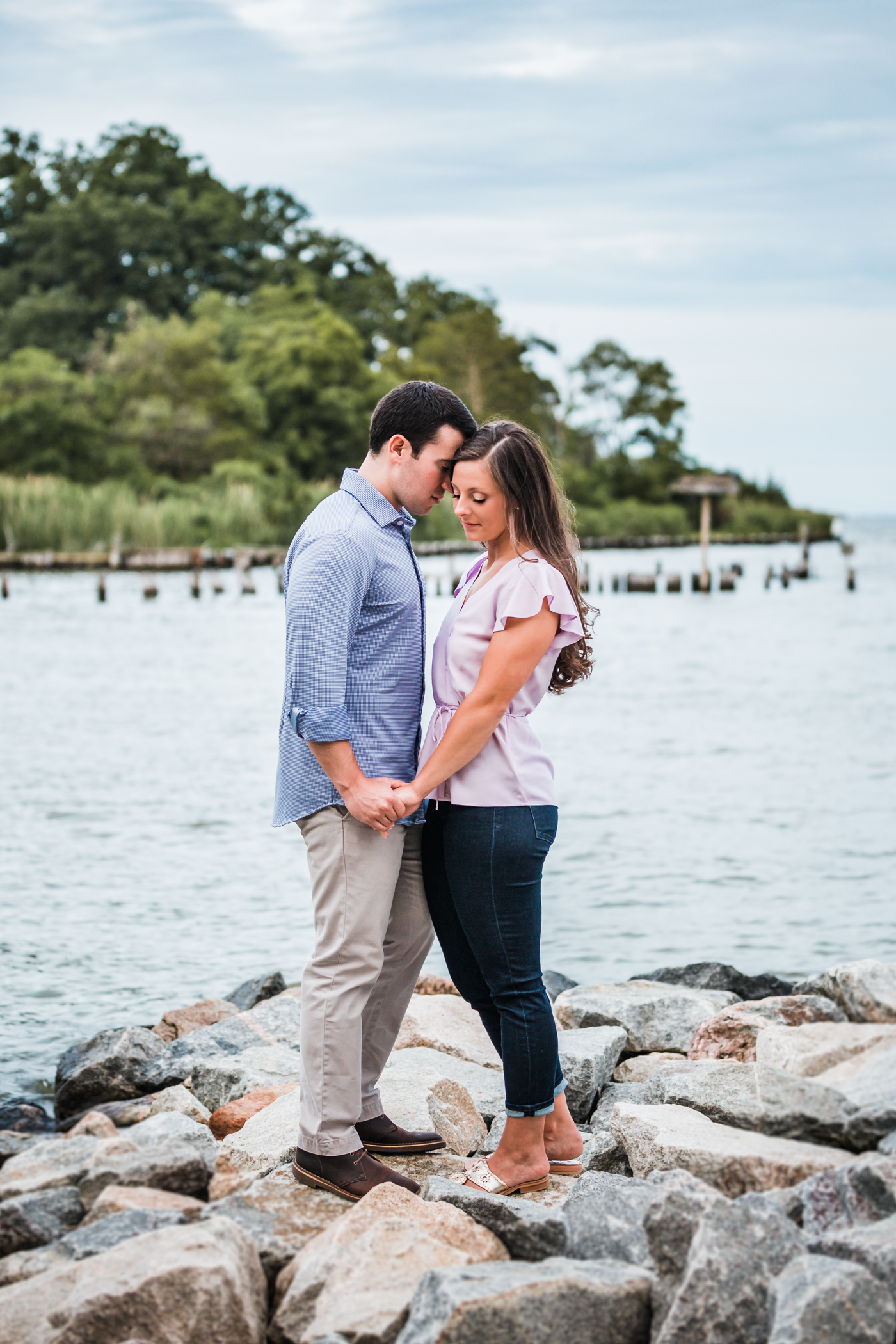 couple stands on the rocks together at Quiet Waters Park - best waterfront locations for engagement photos in Maryland