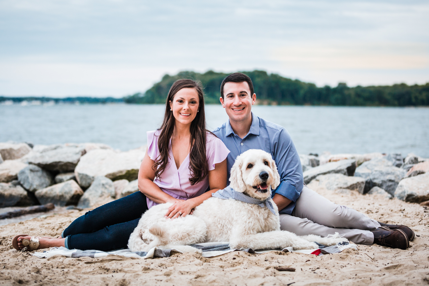 couple sits with their dog, Teddy, during their engagement session in Annapolis, Maryland on the beach