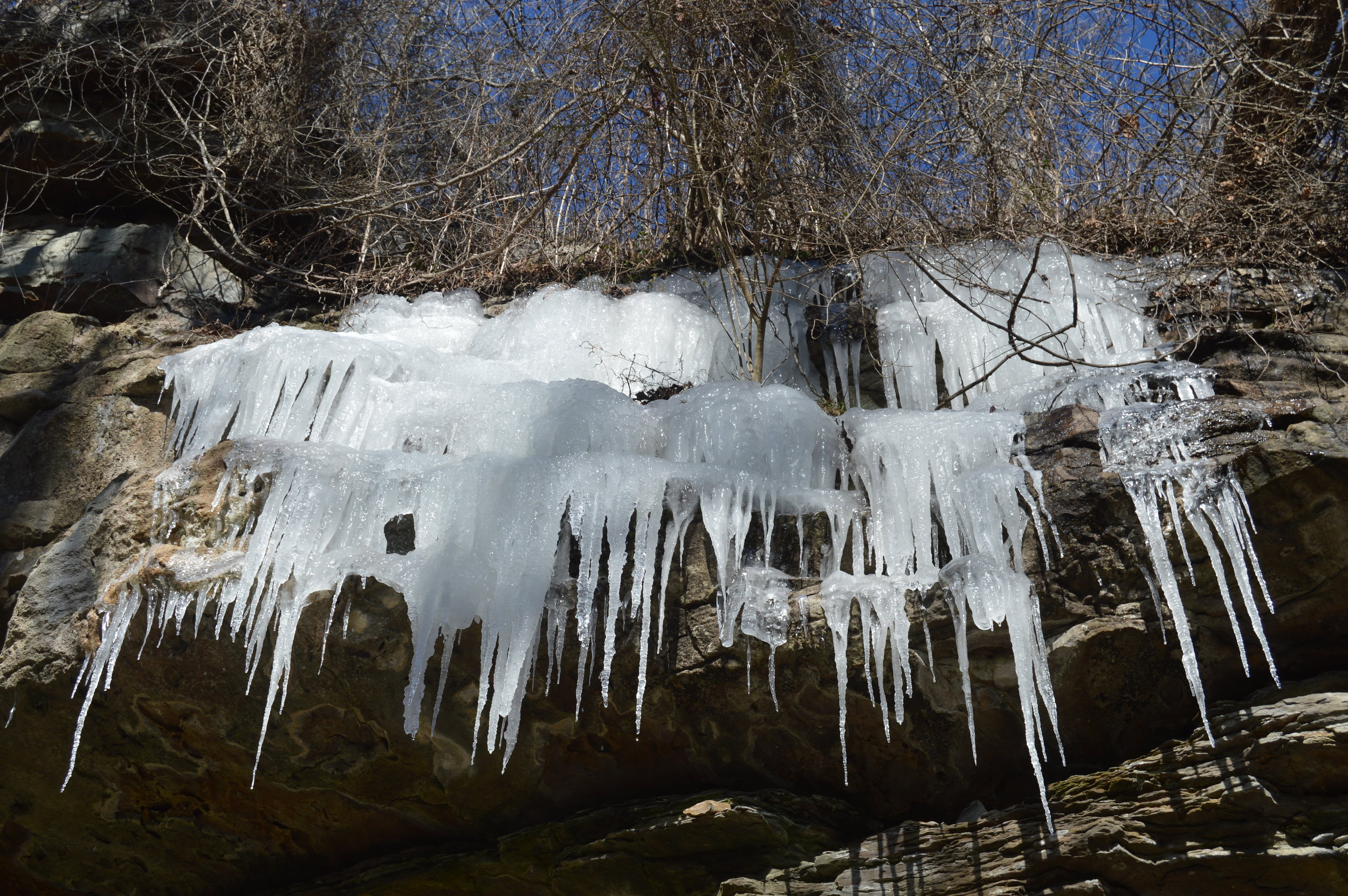 The rock ledges on the trail down to the base of Ozone Falls covered in a wide array of icicles.