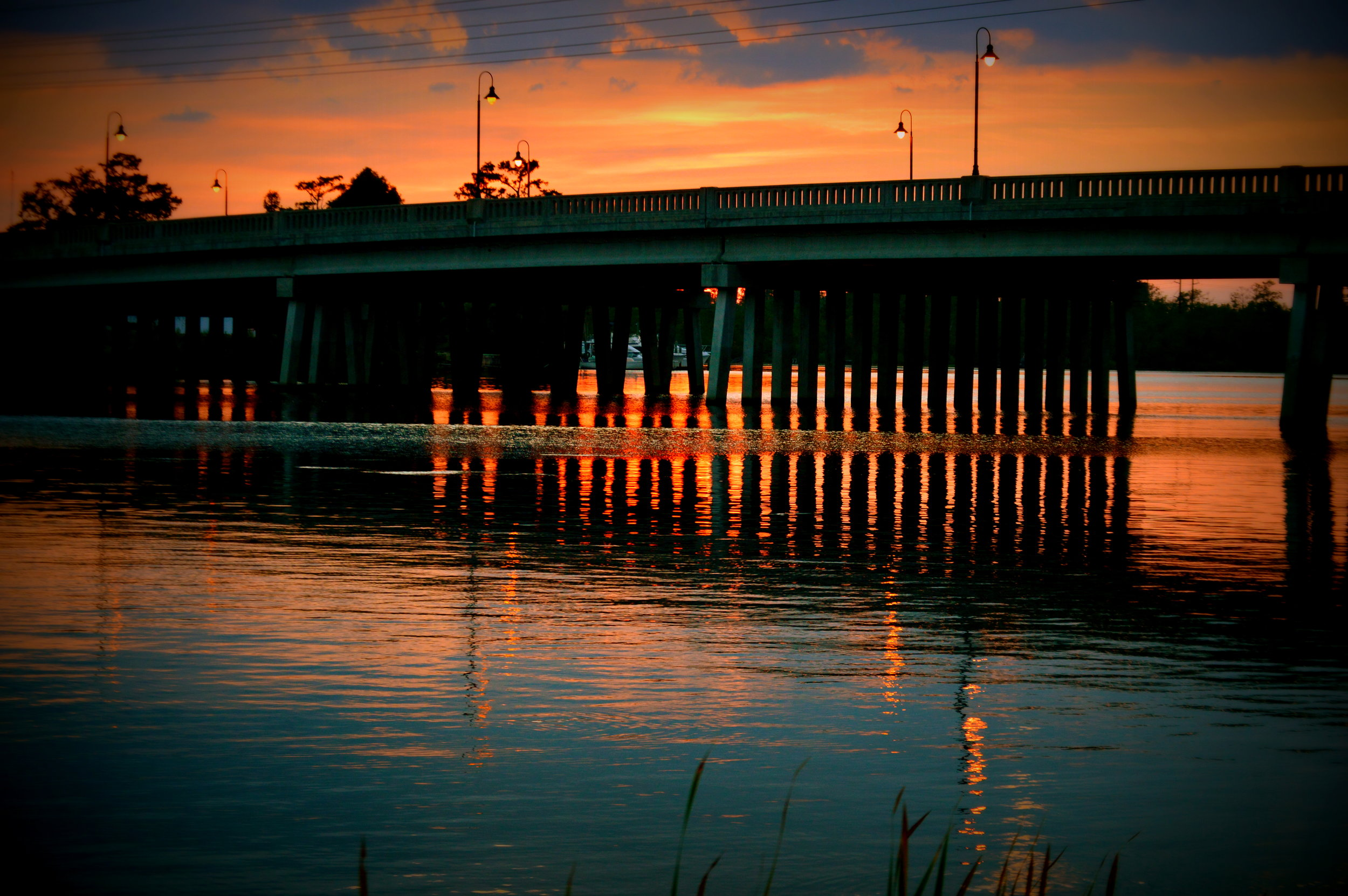 """The New River is the main waterway in Jacksonville, NC. From the riverfront park Downtown you can catch a great sunset at the """"new"""" bridge along the Marine Highway."""