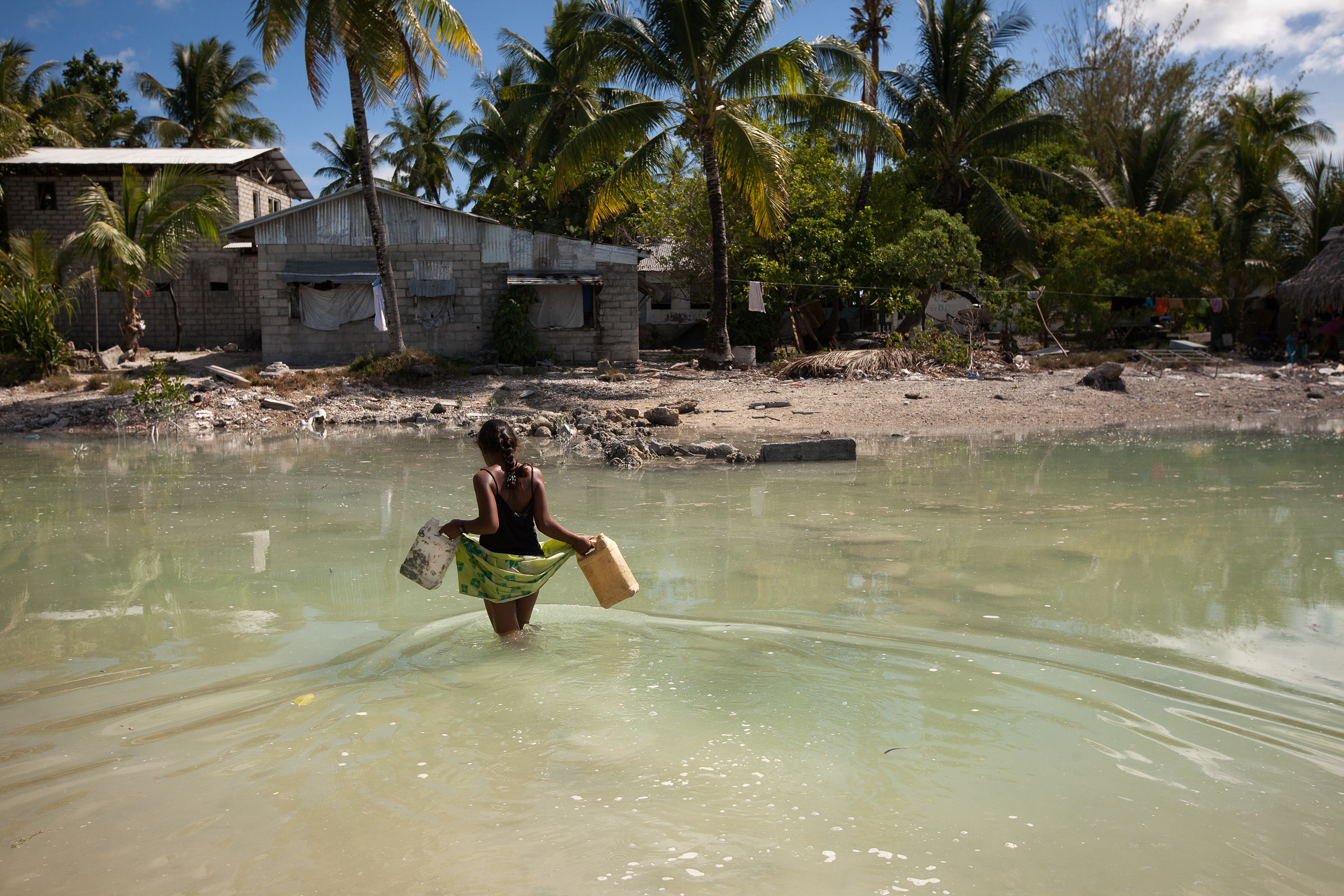 A young girl crosses the lagoon at high tide to get some water for her family who live on a thin strip of sand that gets cut off from the main island every high tide.