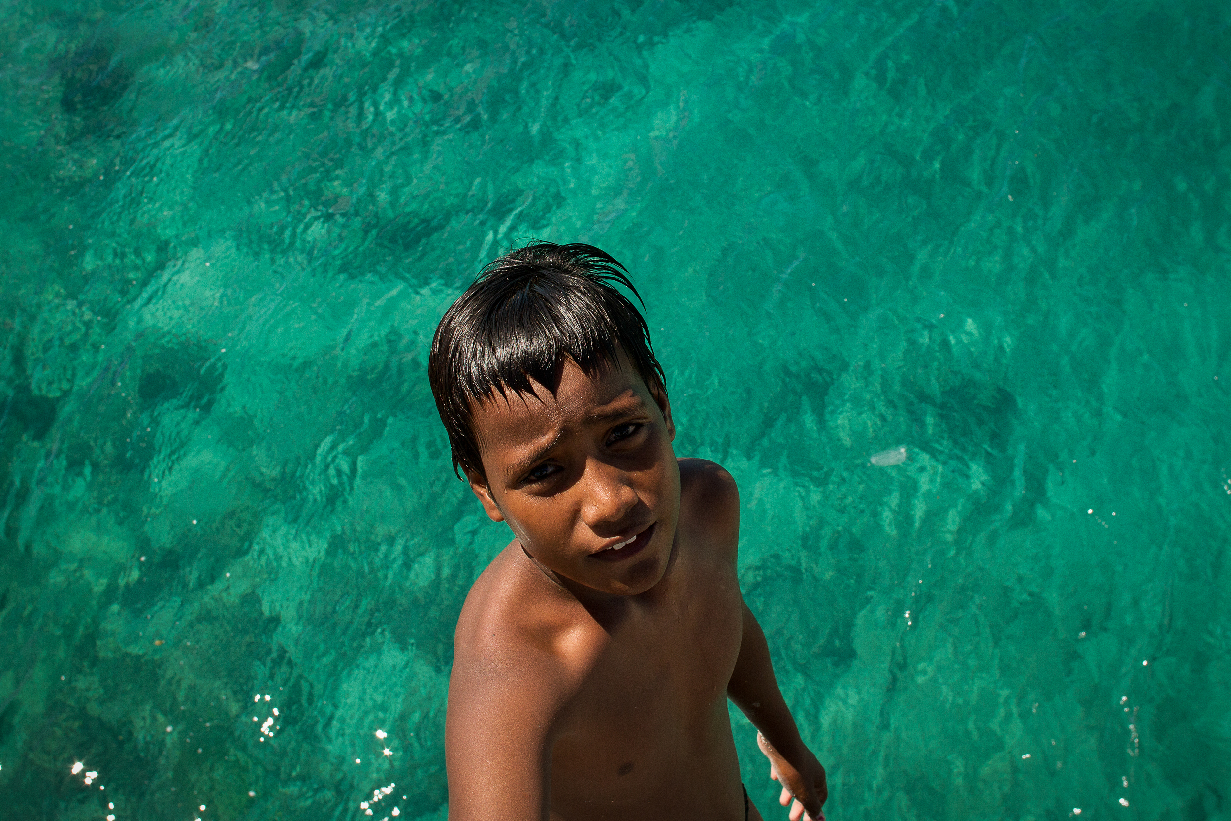 A young boy hangs off a bridge above the water rushing out below. Kiribati is focused on ensuring the youth acquire adequate skills and education to enable them to be able migrate away from their homeland 'with dignity' as the ocean continues to rise, making life in their country untenable.