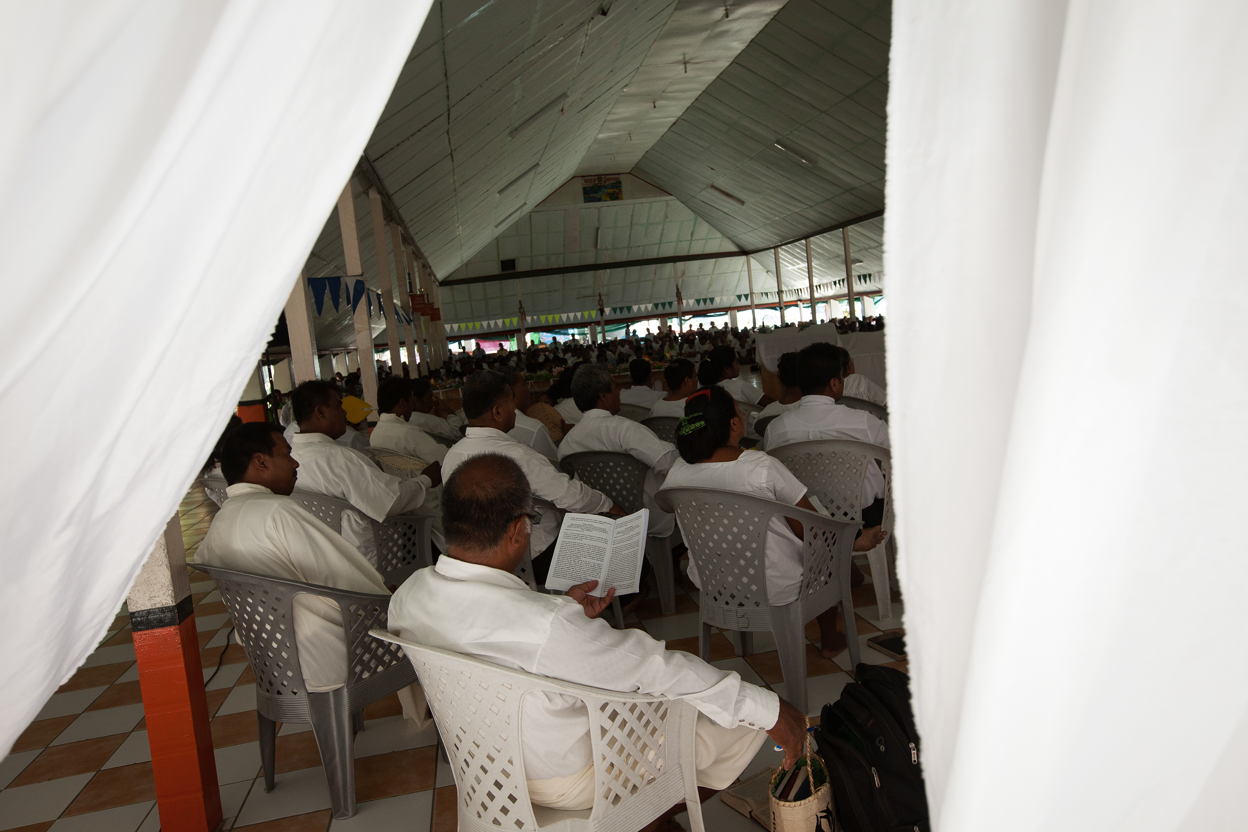 The choir of an Anglican church in Banraeaba, South Tarawa awaits their next hymn. Kiribati is overwhelmingly religious, and the varying religions can have very different attitudes towards the potential impacts of climate change. Some accept the science and work with the community in education about the issue and help with preventative measures, however others deny that God would let their islands disappear.