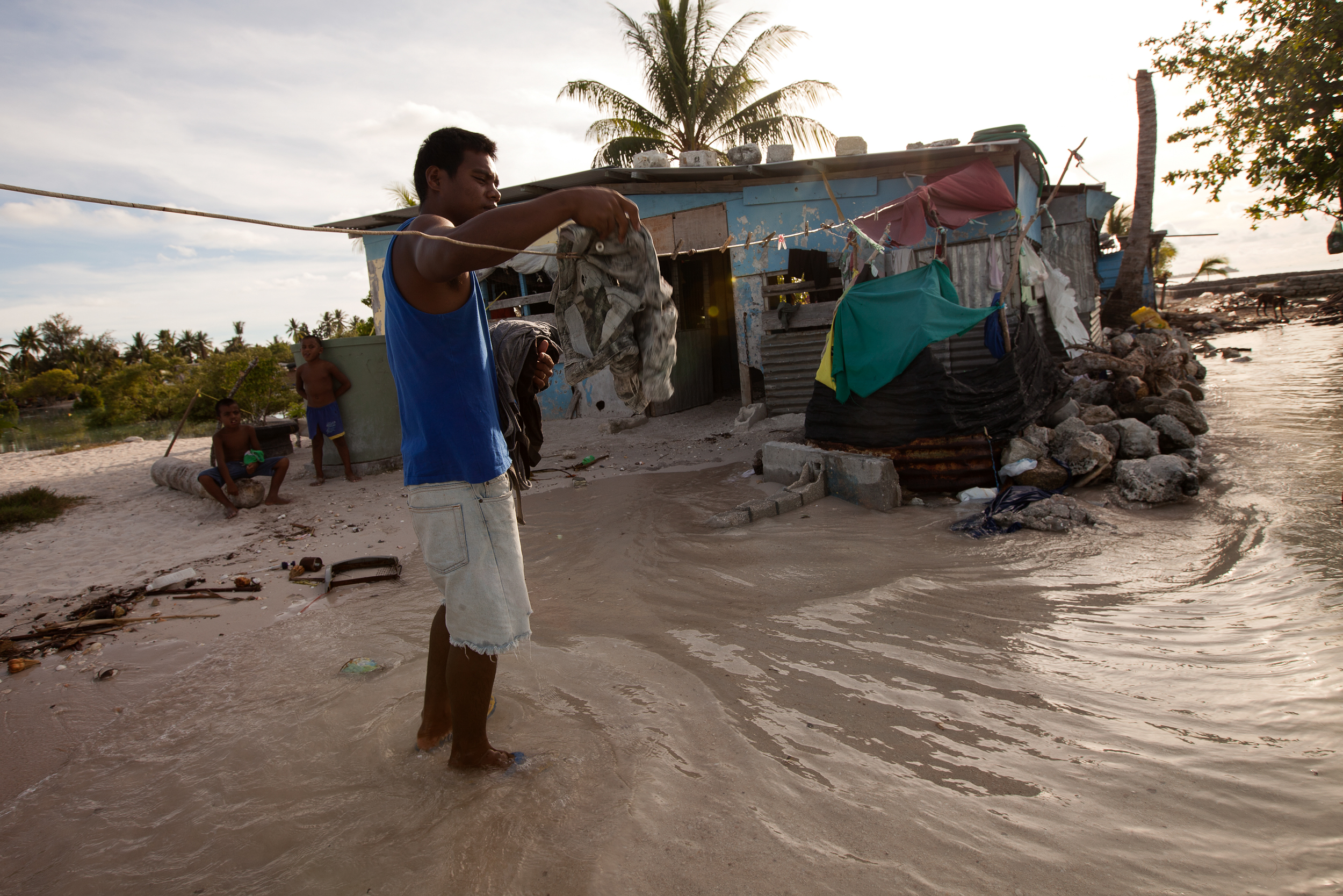 Tokeman Tekaakau brings in his washing as the waves lap around his ankles next to his house in Golden Beach. Tokeman said there used to be three more houses in front of his that had to be pulled down and relocated because the ocean continuously eroded the land away from under them.