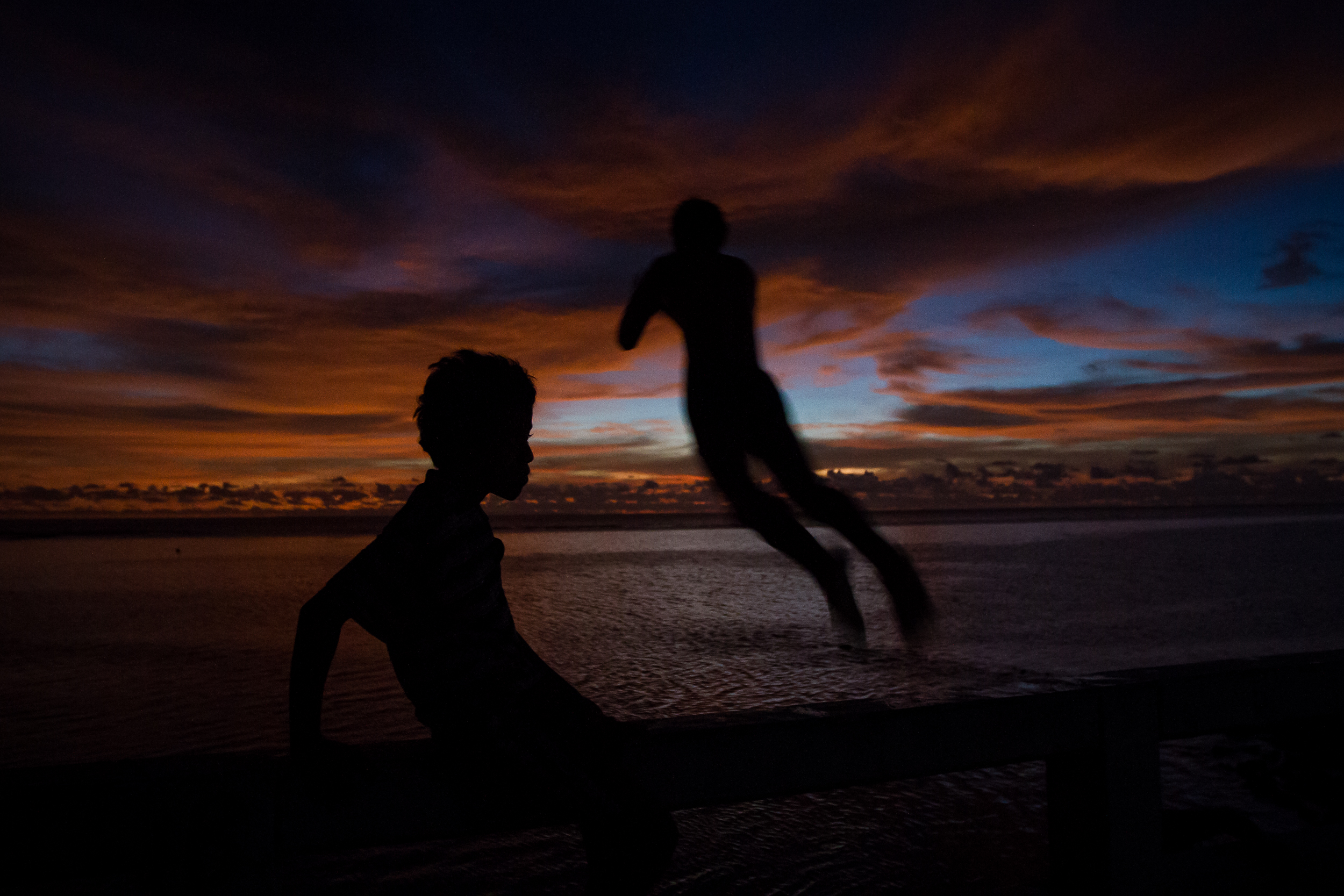 As the tide comes in and the sun sets, a young boy gets in one final jump from a bridge in Tarawa. Without a similar Compact to ensure free passage to another country, the Kiribati people have no idea where they would end up should their country become unliveable in the coming years.